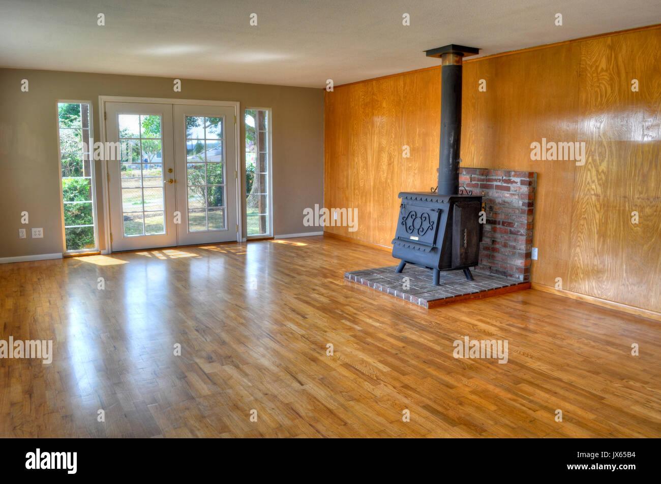 innere leere wohnzimmer eines hauses mit franz sischen glast ren hartholzb den und ein holzofen. Black Bedroom Furniture Sets. Home Design Ideas