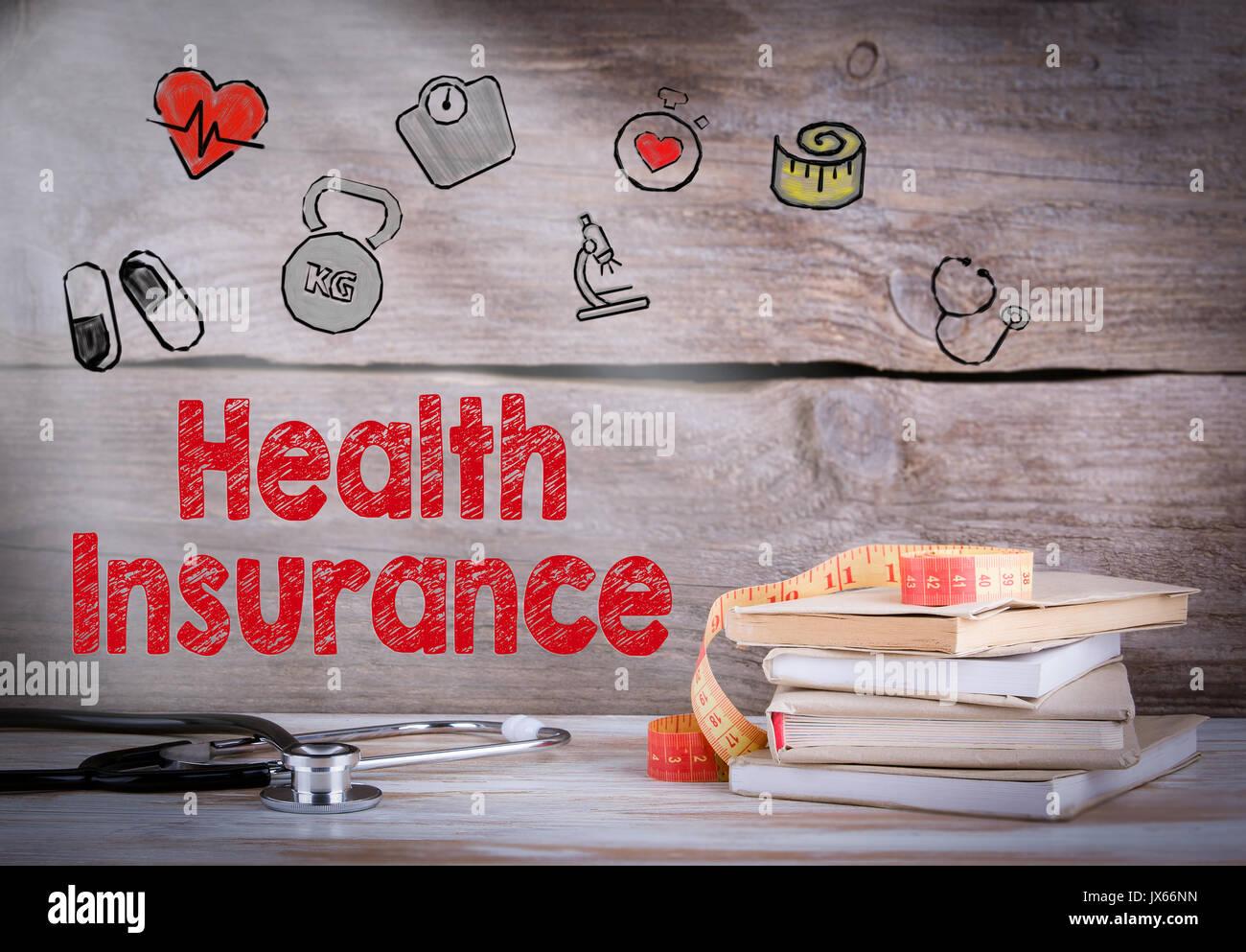 Krankenversicherung Konzept. Stapel von Büchern und ein Stethoskop auf einer hölzernen Hintergrund. Stockbild