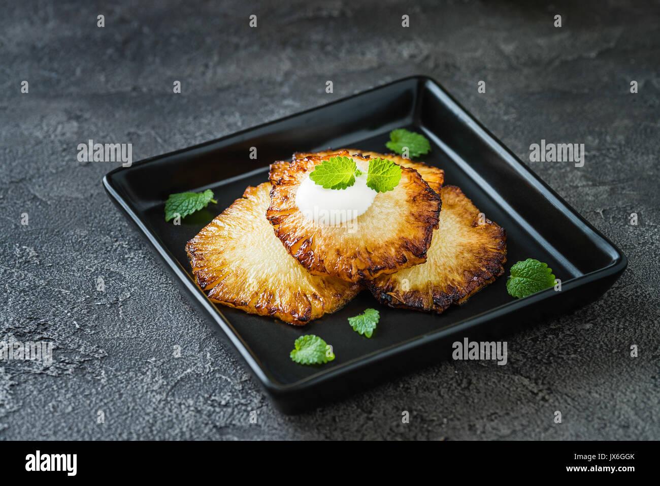 Gebratene Ananasscheiben mit Creme fraiche, Minze in Schwarz quadratische Platte auf dunklem Hintergrund Stockfoto