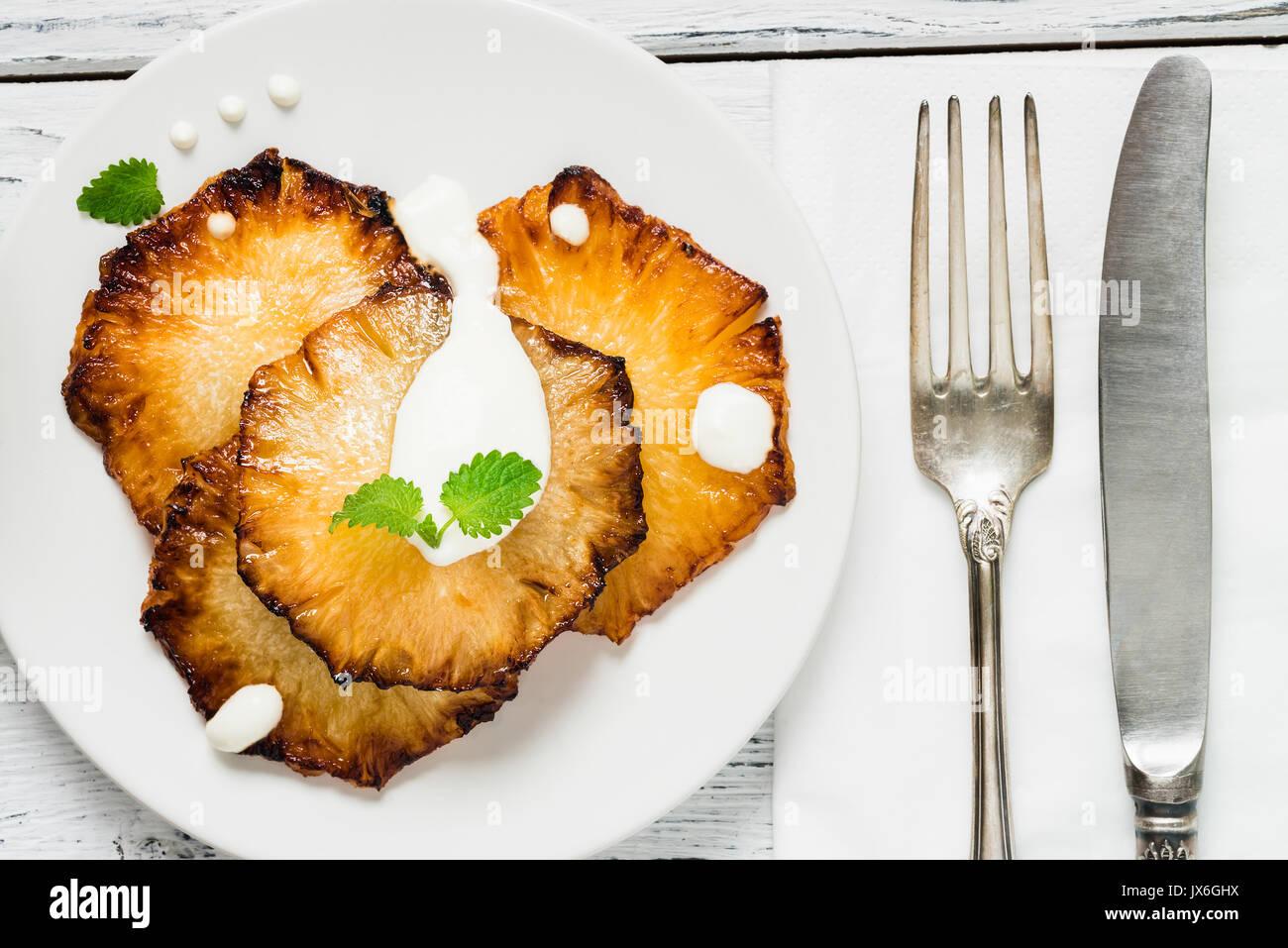 Gebratene Ananasscheiben mit Creme fraiche, Minze in Weiß Platte auf Holz- Hintergrund. Ansicht von oben Stockfoto