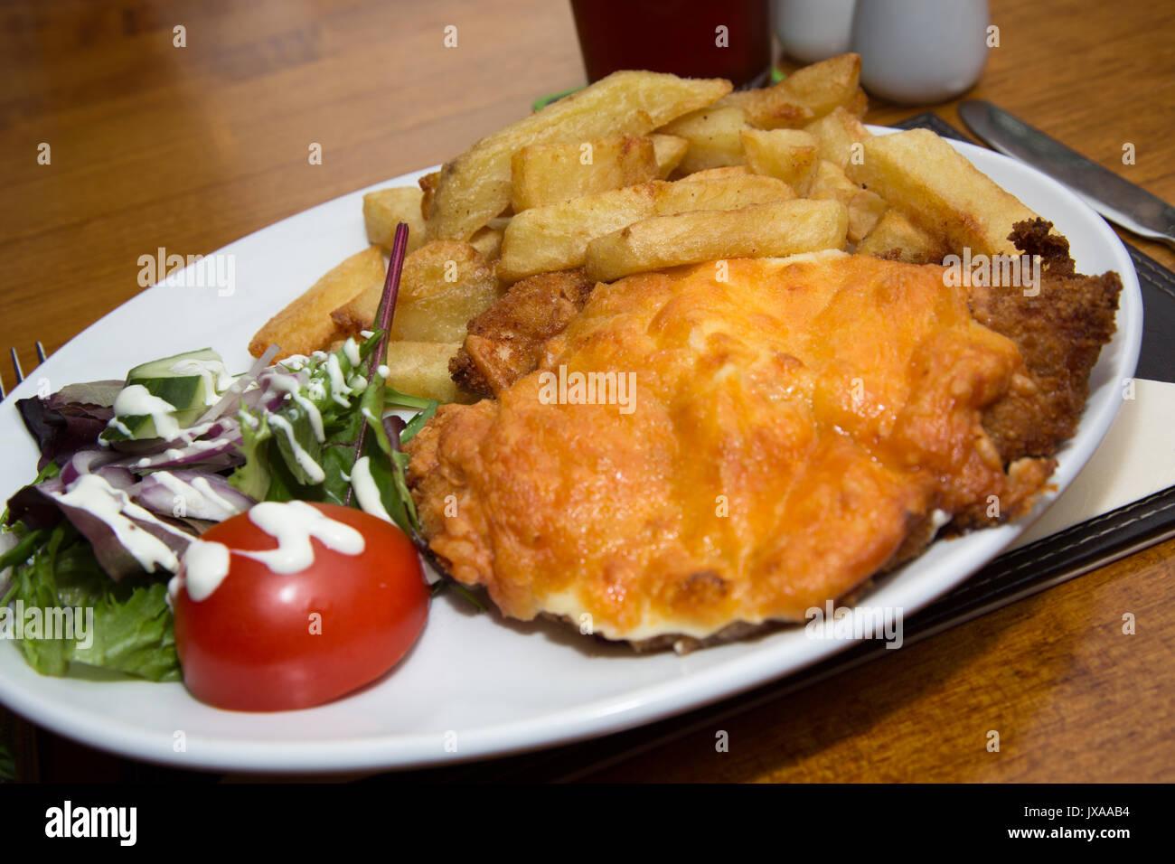 Huhn Parmo serviert zum Mittagessen in einem englischen Pub/Bar/Restaurant mit einem Pint Ale. Stockbild