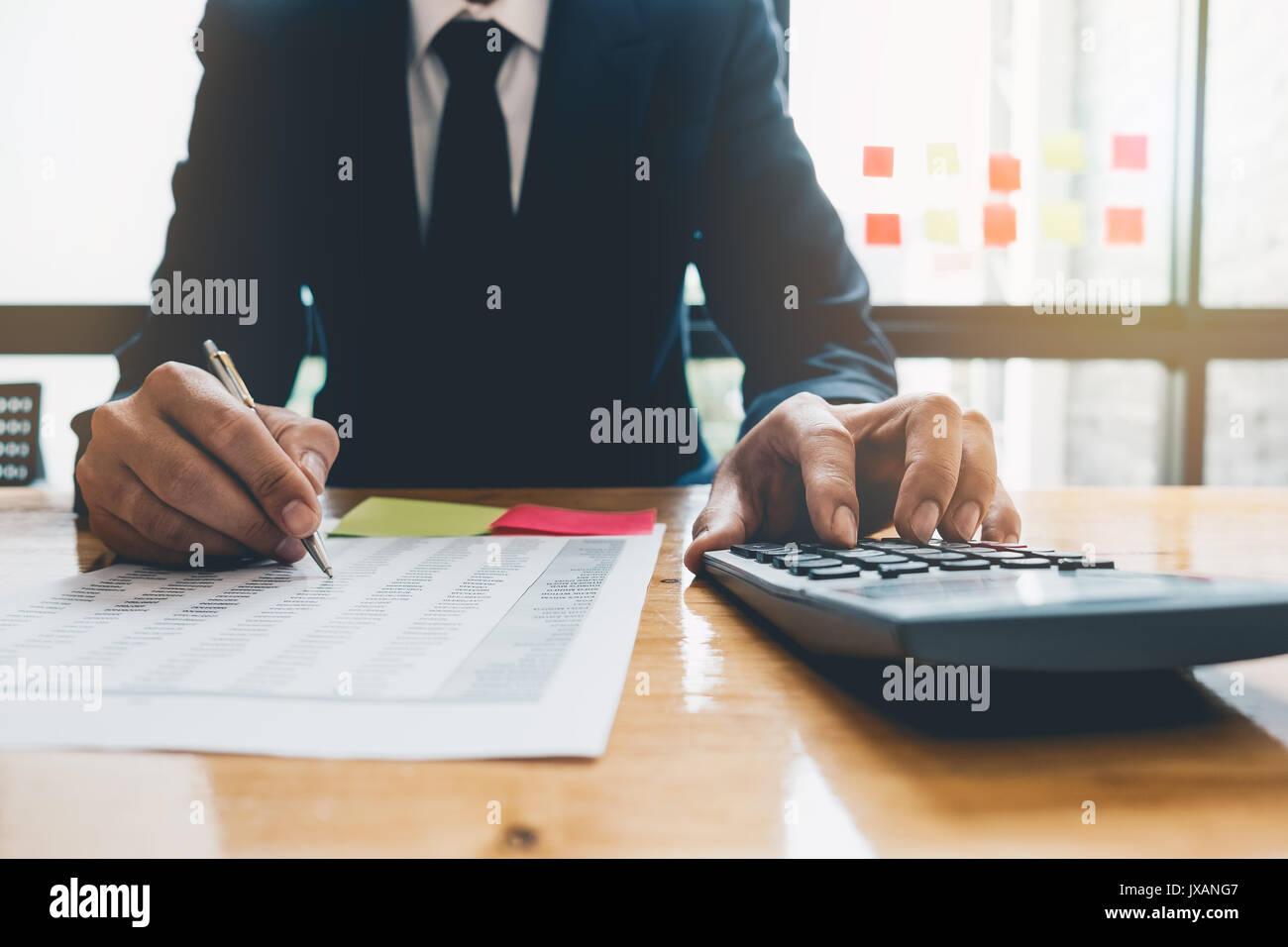 in der Nähe Konten, Business Mann oder Rechtsanwalt Steuerberater arbeiten auf Verwendung eines Taschenrechners und schreiben auf Dokumente Stockbild