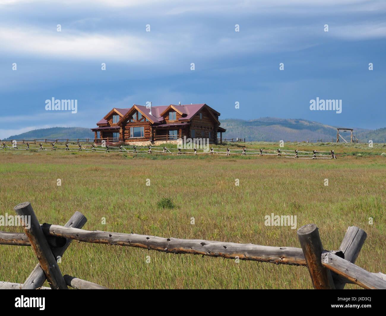 Blockhaus Haus auf einer Wiese in ländlichen Colorado in den Rocky Mountains zu bewahren. Hinter dem Haus gibt es Berge. Die prairi Stockbild