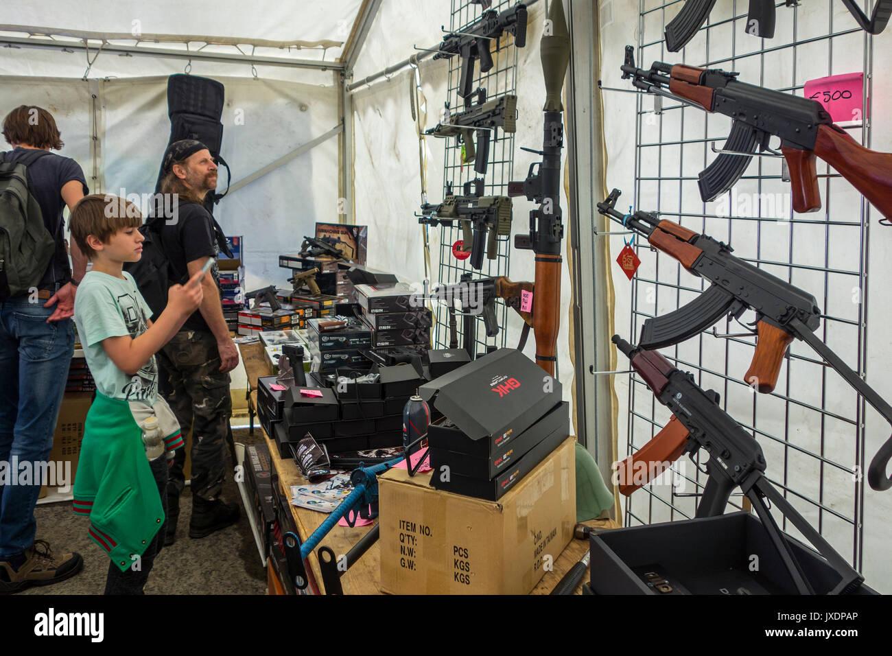 Kind und Besucher, die beim airsoft Waffen zum Verkauf suchen, waffennachbildungen entworfen, realistisch zu echten Feuerwaffen bei militaria Messe ähneln Stockbild