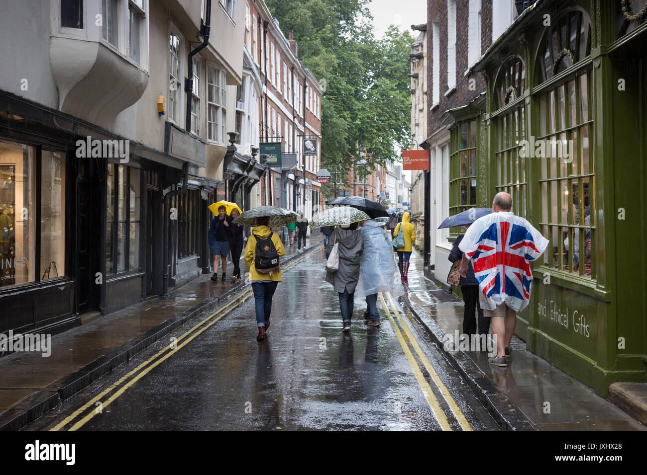 Sehr regnerischen Tag im Zentrum von York, Sonnenschirme und einen Mann, der in einer Union Flag anorak Poncho Stockbild