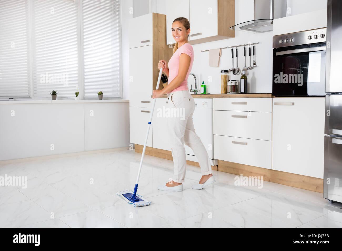 Fußboden In Der Küche ~ Lächelnde frau mit mop reinigung reinigung fußboden in der küche