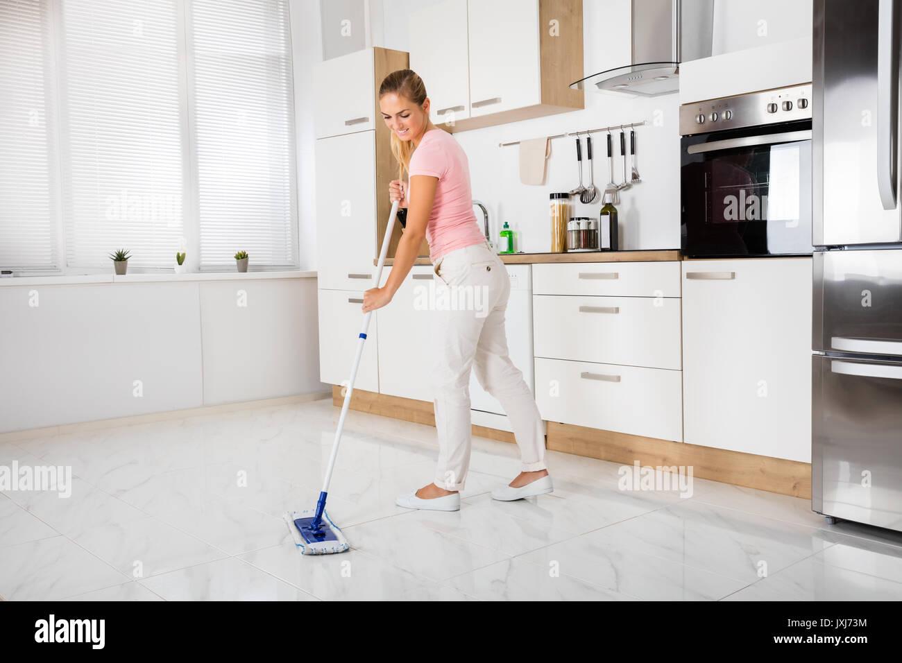 Welcher Fußboden Küche ~ Lächelnde frau mit mop reinigung reinigung fußboden in der küche