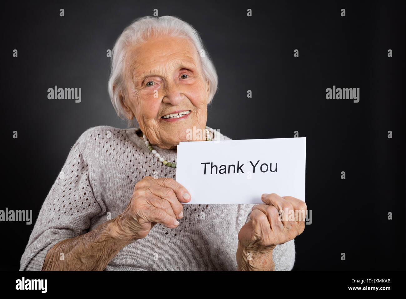 Portrait von lächelnden älteren Frau, vielen Dank Karte Über grauer Hintergrund Stockbild