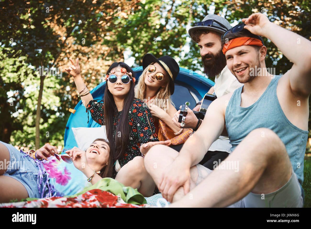 Fünf junge erwachsene Freunde spielen akustische Gitarre während Festival Camping Stockbild