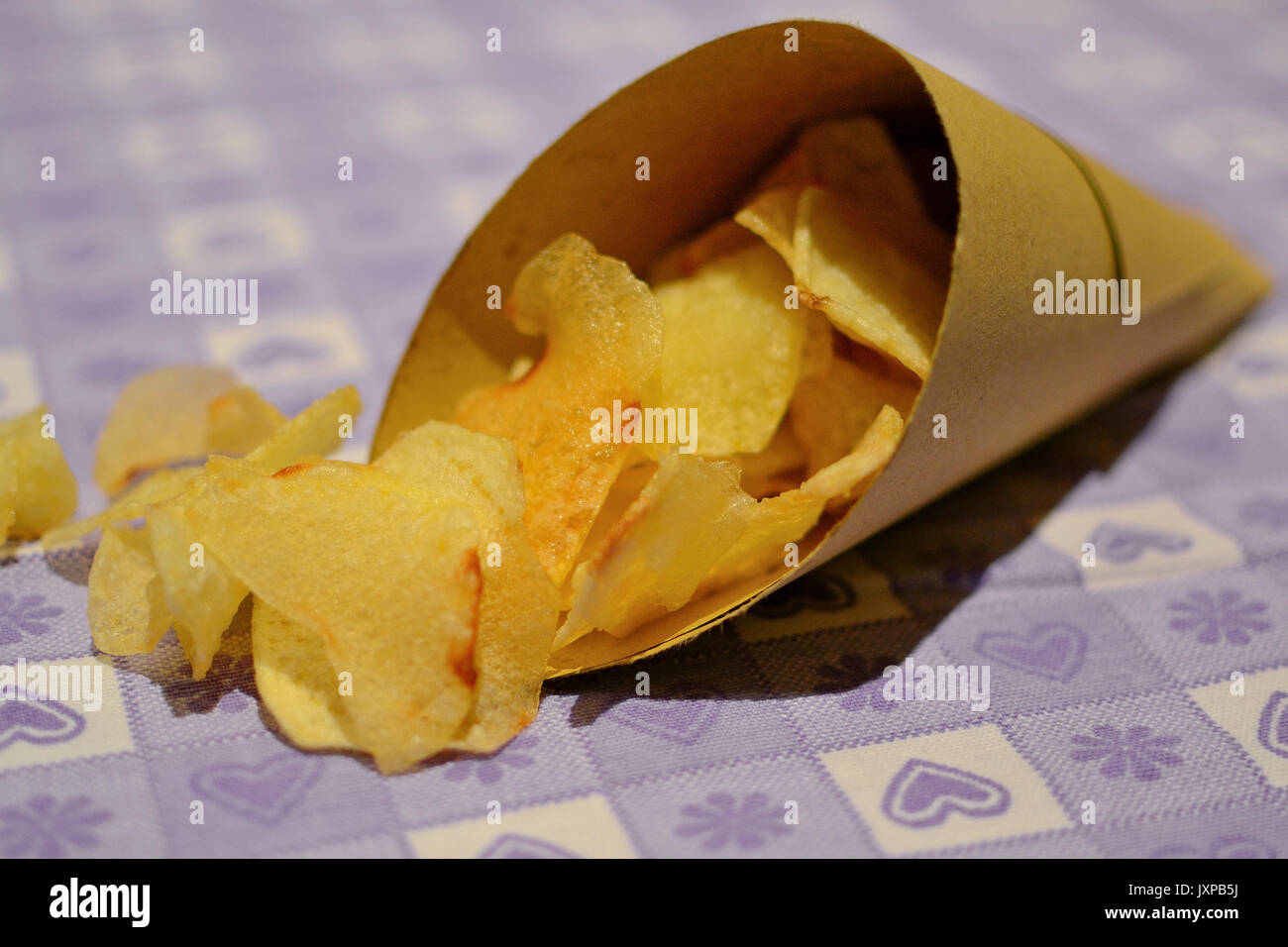 Nahaufnahme, Seite, Ansicht von Kartoffelchips in einem Papier Kegel auf einem Tisch mit einem lila dekorierten Stockbild