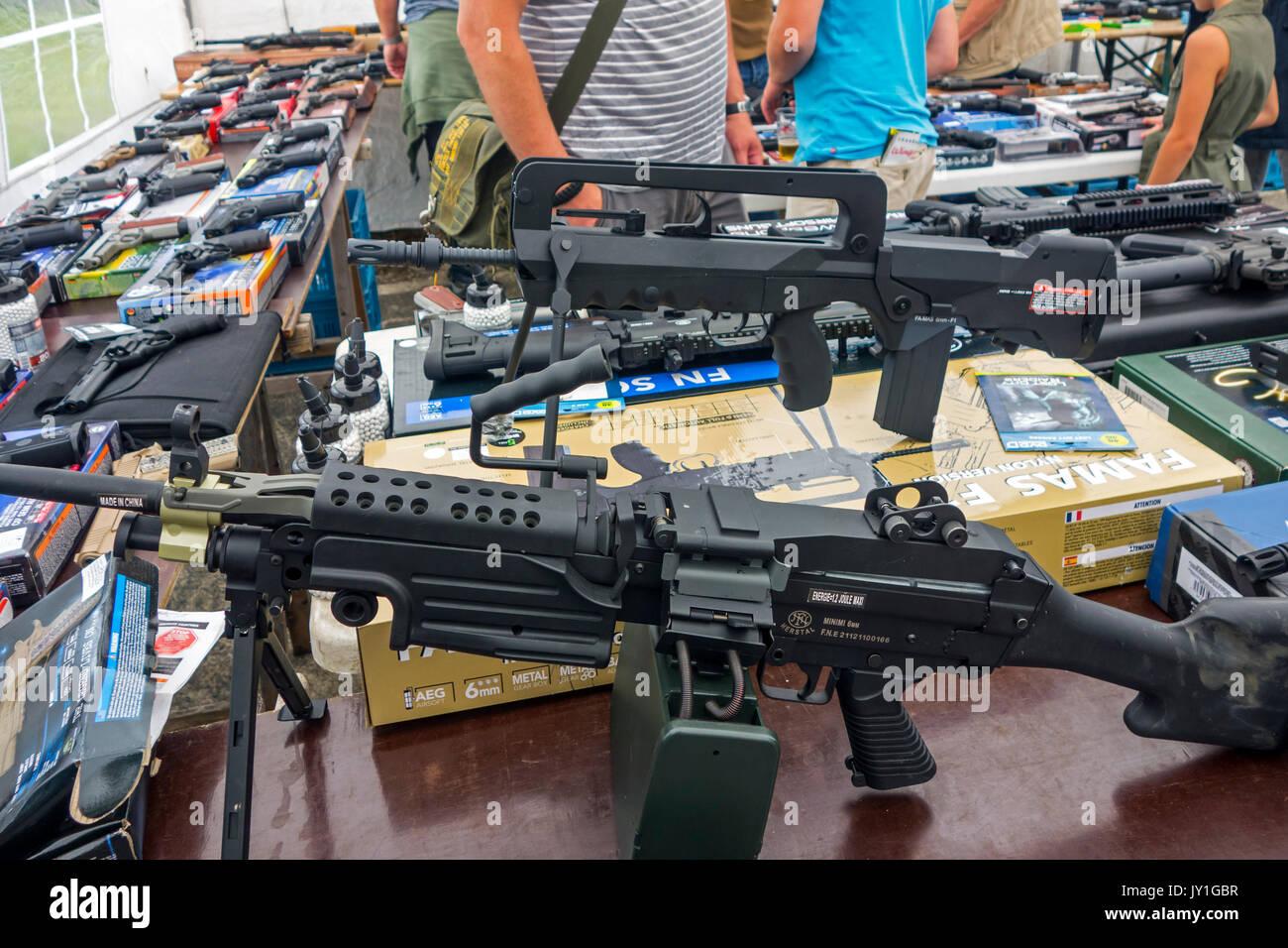 Bei militaria Messe verkaufen airsoft Waffen stehen, waffennachbildungen, die echten Schusswaffen wie FN Minimi M249 SAW und FAMAS-F1 realistisch ähneln Stockbild