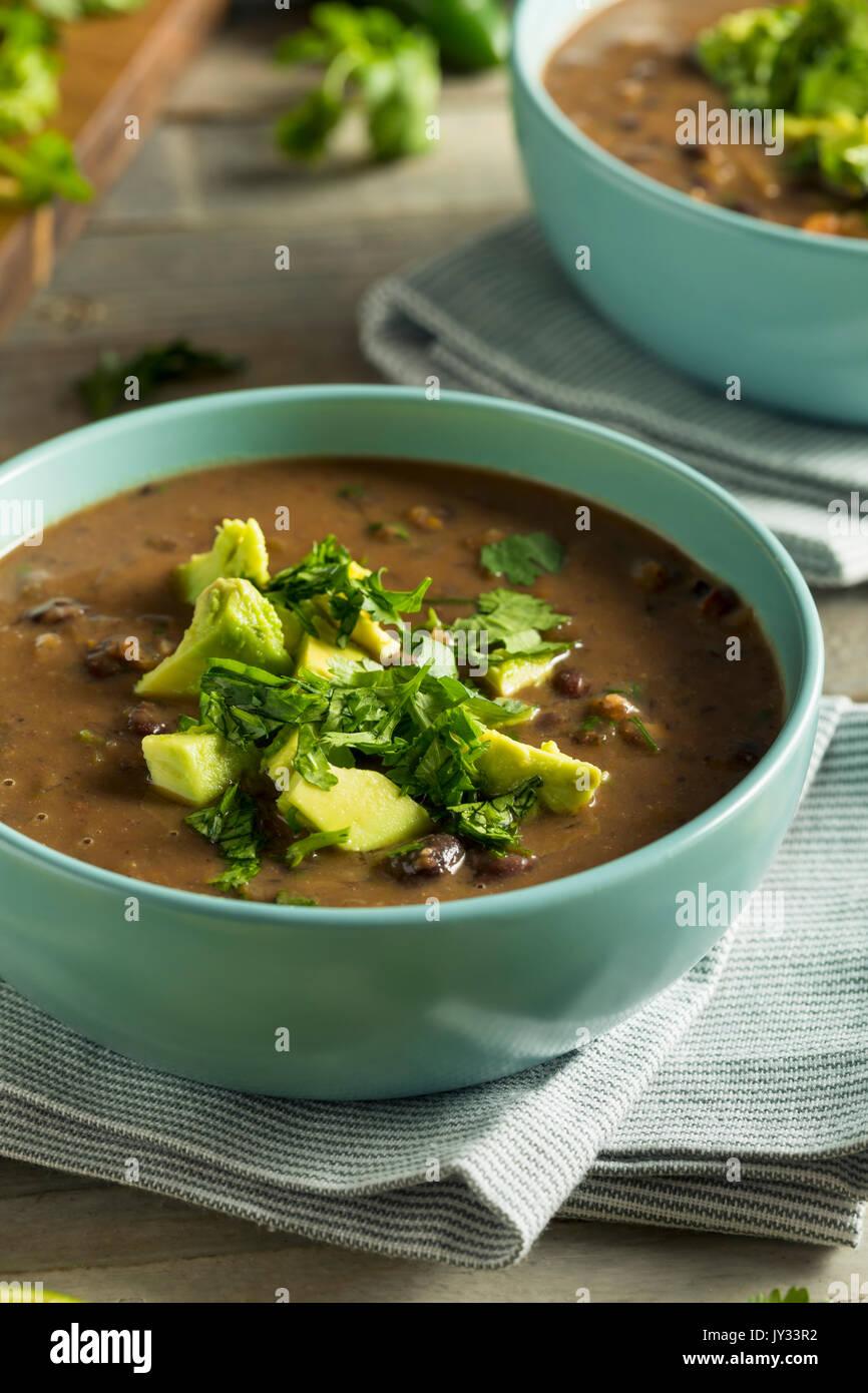 Frische hausgemachte schwarze Bohnensuppe mit Avocado und Koriander Stockfoto