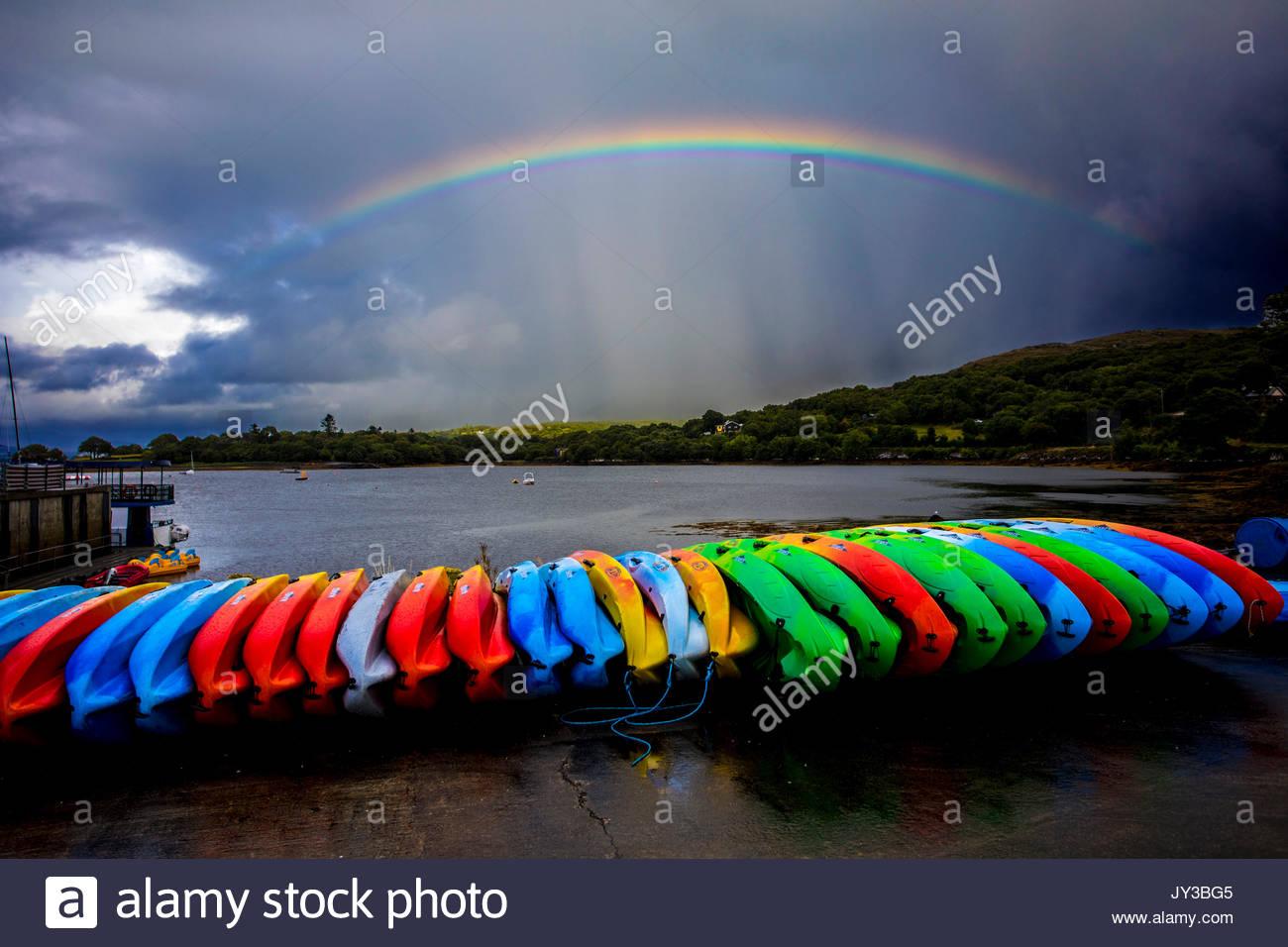 Regenbogen über bunten Kajaks Stockbild