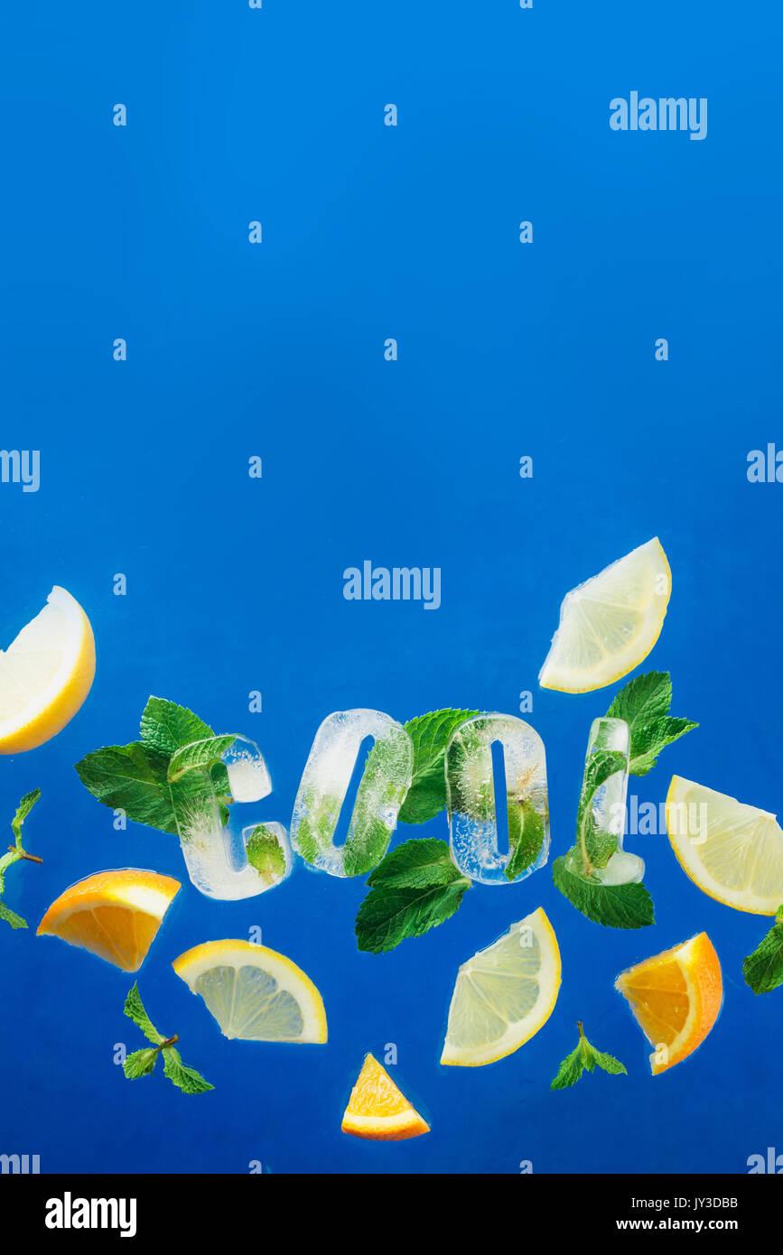 Ice Cube Schriftzug mit gefrorenen Minze, Zitronenscheiben und Orangen auf blauem Hintergrund. Text sagt Cool. Stockbild
