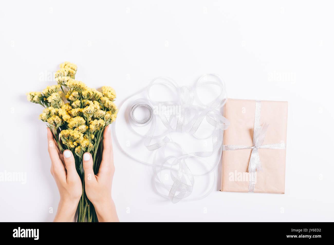Weibliche Hände Verpackung der Geschenke und einen Strauß gelber ...
