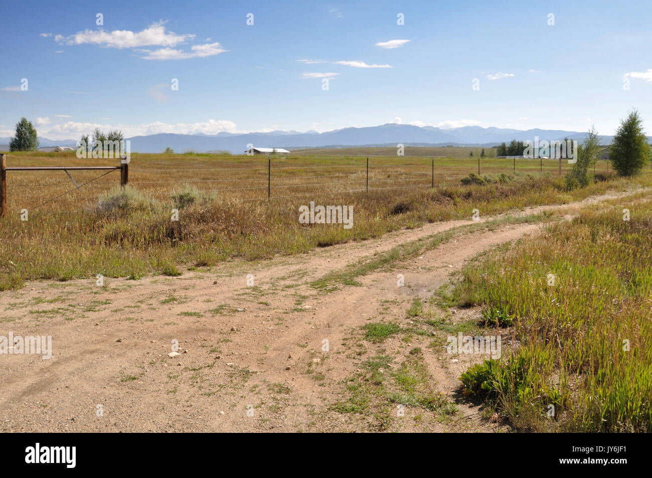 Schmutz der Straße von einer Wiese in Colorado. Die Rocky Mountains sind im Hintergrund. Stockbild