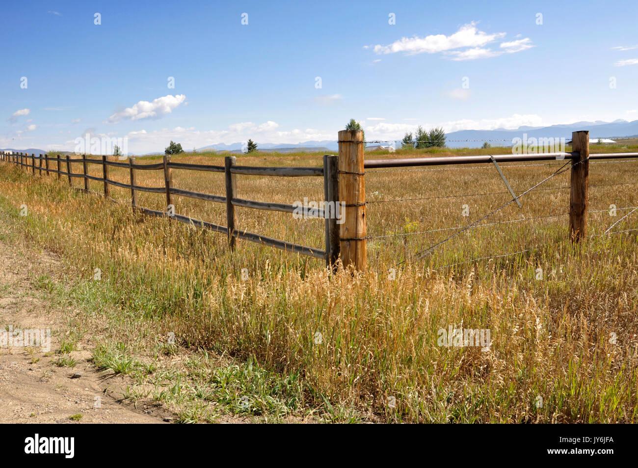 Holz und Draht Zaun von einer Wiese in Colorado. Die Rocky Mountains sind im Hintergrund, Stockbild