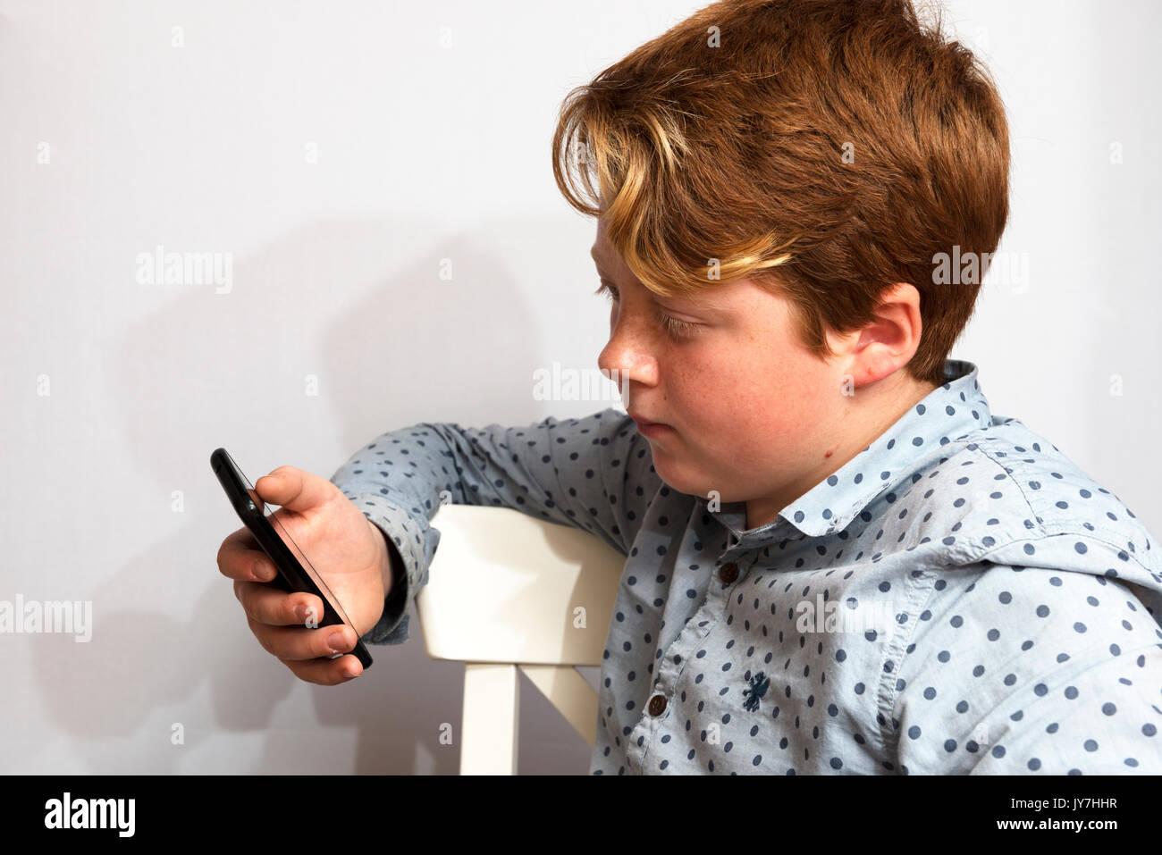 11-jähriger Junge mit Smartphone Stockbild