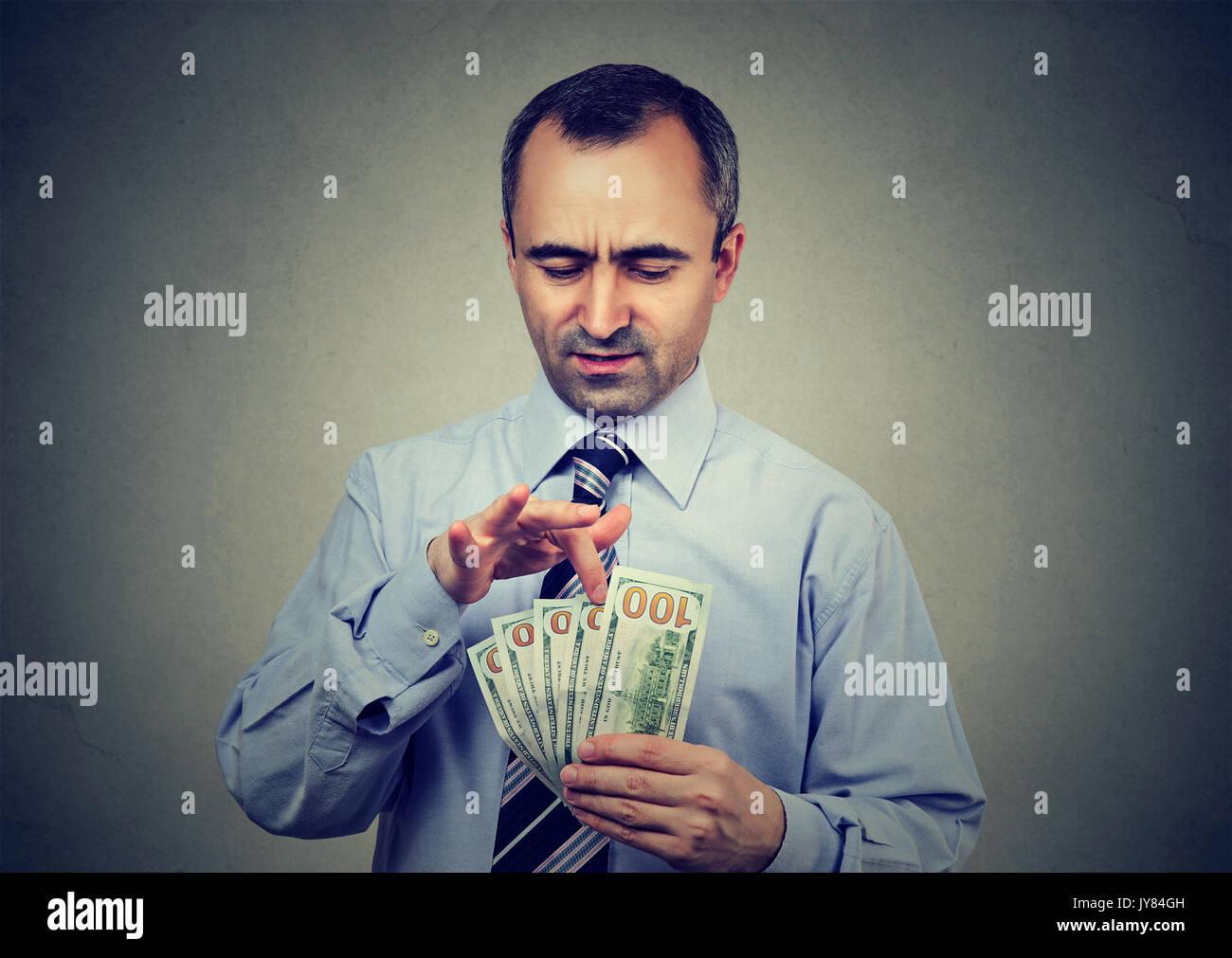 Ausgereifte Mann zählen Geld auf grauem Hintergrund Stockbild