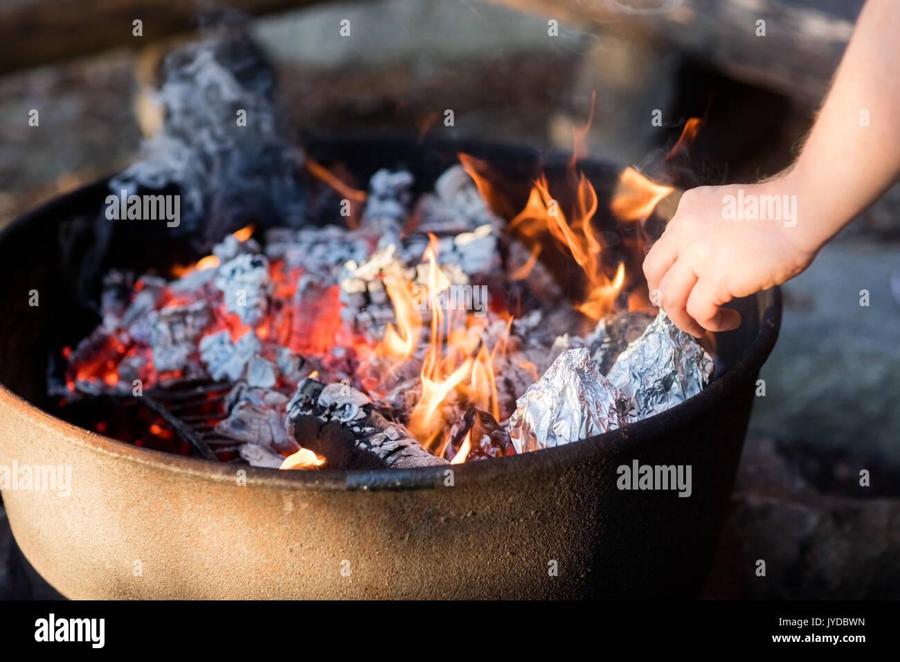 Nahaufnahme der Hand Grillen, DIE VON EINER FOLIE UMHÜLLT WIRD Auf der Feuerstelle Stockbild
