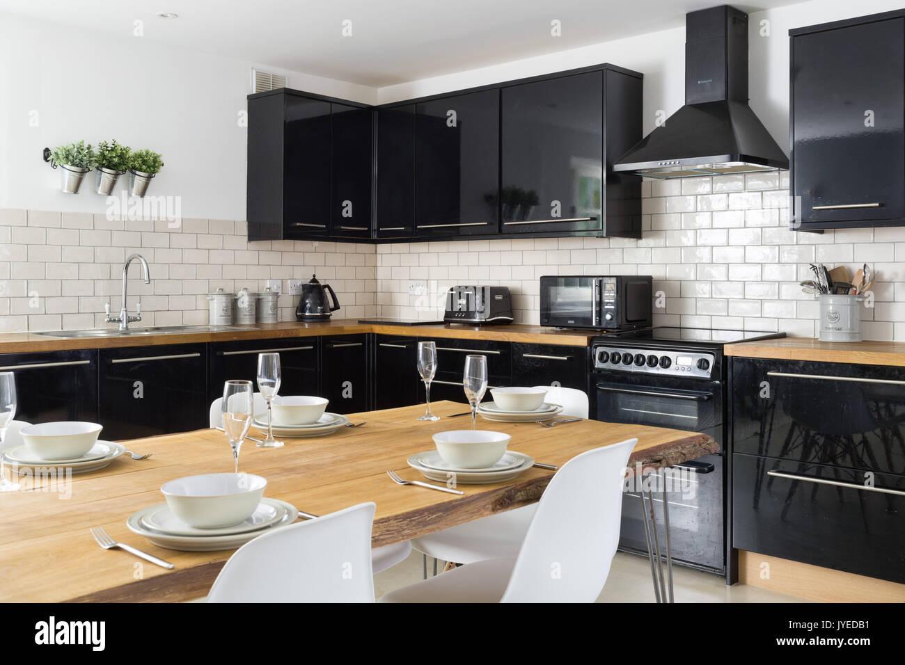 Eine moderne Küche mit glänzend schwarzen Schränke, massive Eiche ...