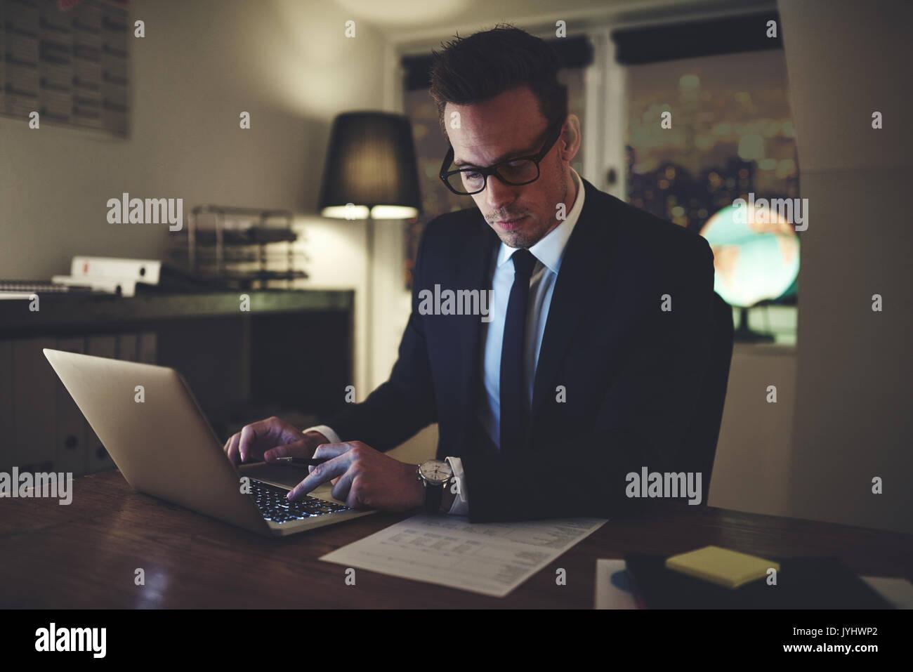 Geschäftsmann Arbeiten konzentrierten sich auf Dokumente in der Nacht, Überstunden im Büro Stockfoto