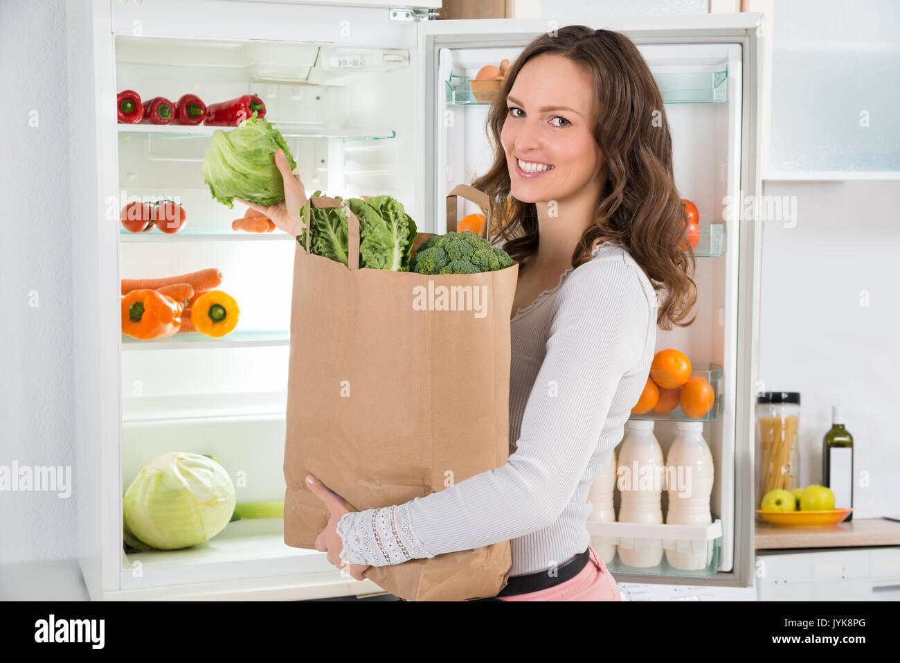 Happy Woman Holding Einkaufen Tasche mit Gemüse vor dem offenen Kühlschrank Stockfoto