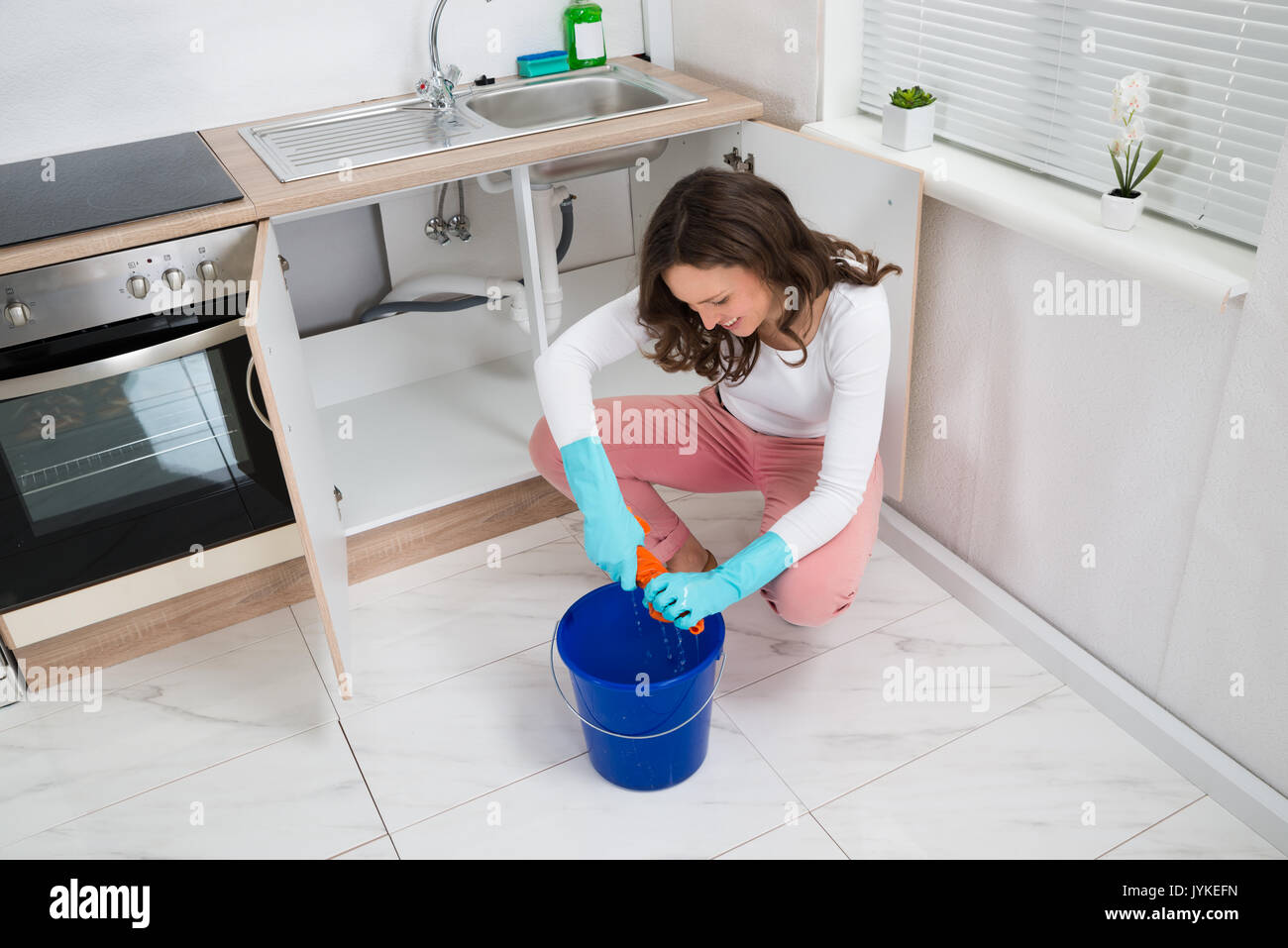 Junge Frau Quetschen Nasses Tuch In Blau Schaufel Auf Küche Zimmer