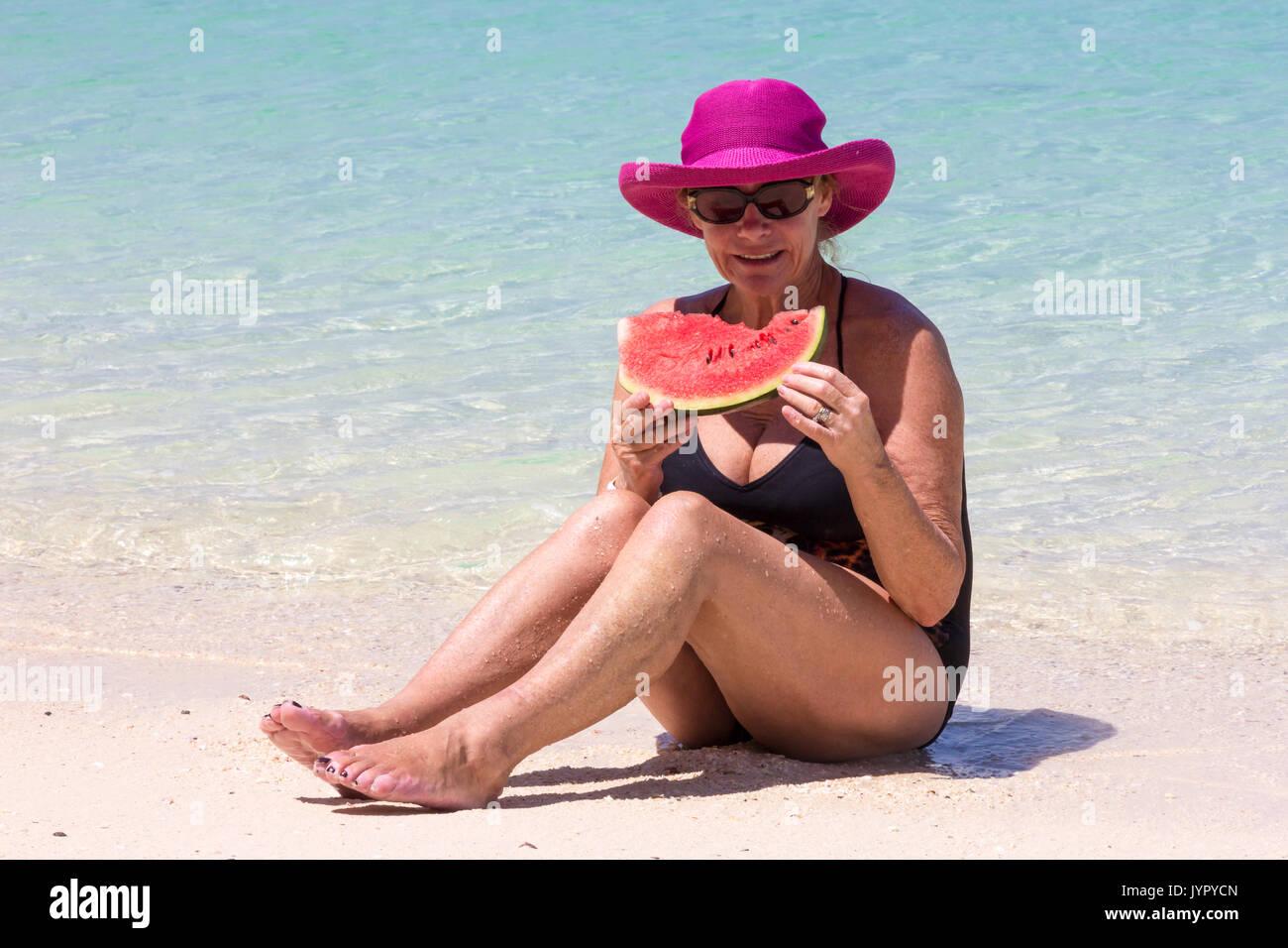 Ältere Frau mit rosa Hut mit Wassermelone im Meer sitzen, Koh Lao Liang, Trang, Thailand Stockfoto