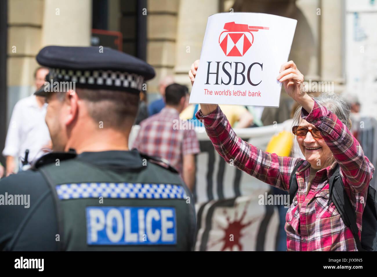 """Demonstrant hält ein Schild da, auf Protest von oben scharf Israel"""" außerhalb der HSBC Bank in Brighton, East Sussex, England, UK. Stockbild"""