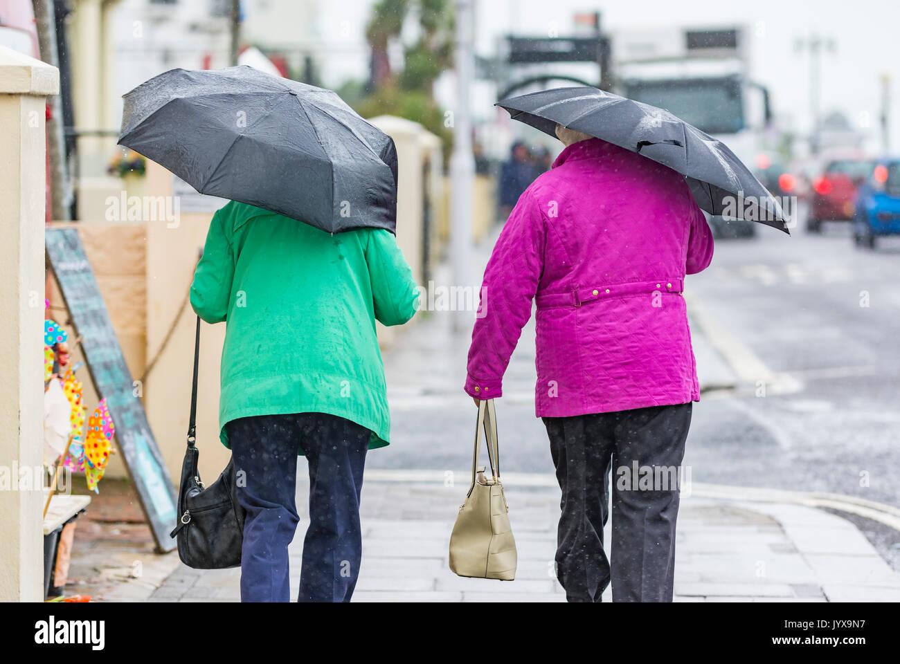 Ansicht der Rückseite des Menschen zu Fuß im Regen mit Sonnenschirmen. Stockbild
