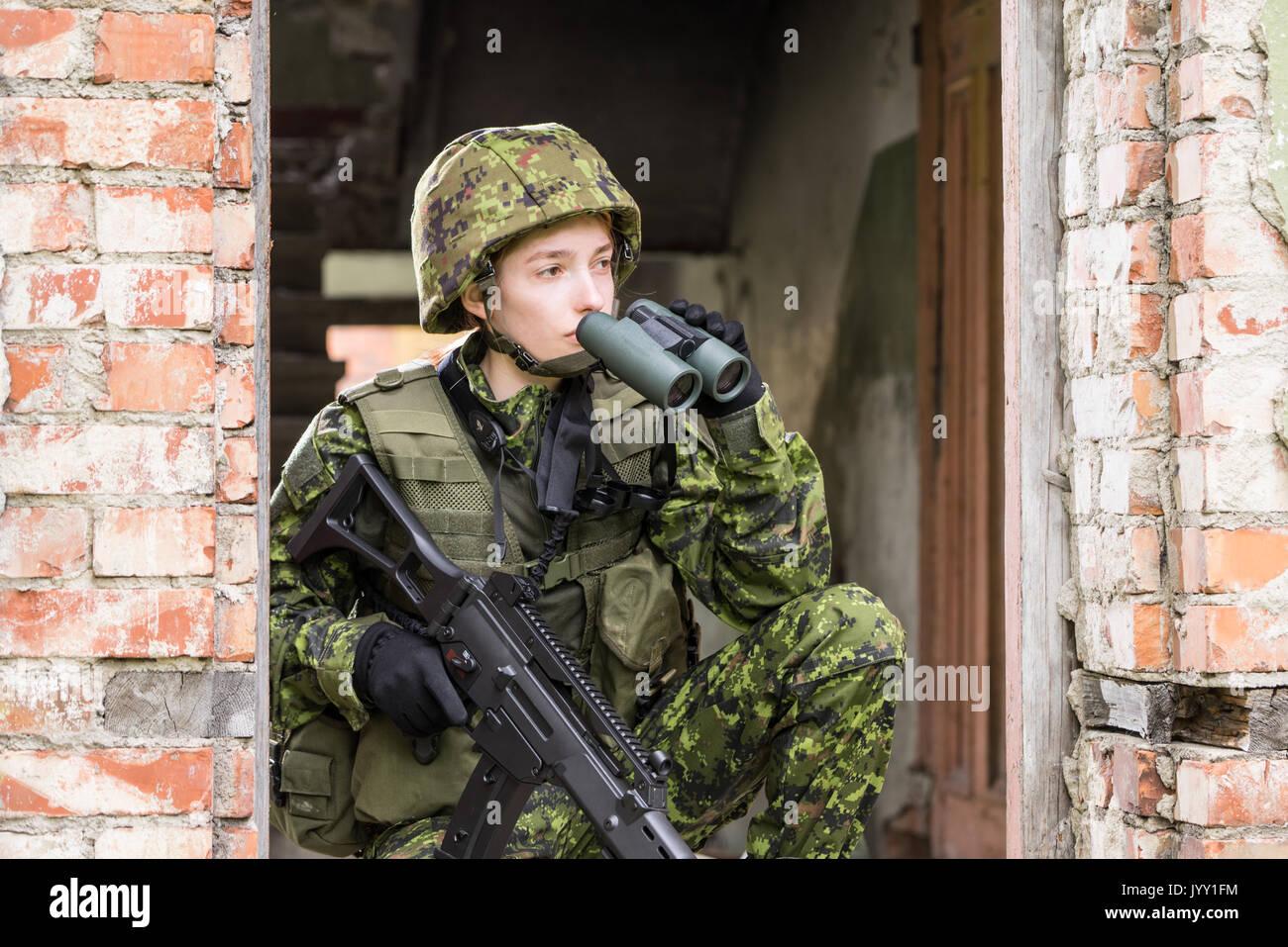 6e0d72948407 Portrait von bewaffneten Frau mit Camouflage. Junge weibliche Soldaten mit  dem Fernglas beobachten. Kind