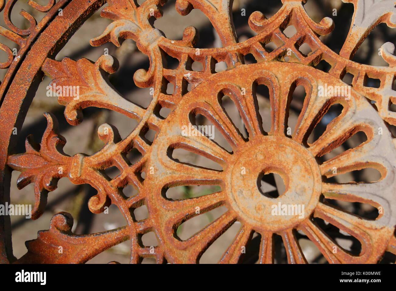Alter rostiger, romantischer, Stuhl aus Metall, mit verspielten Ornamenten Stockbild