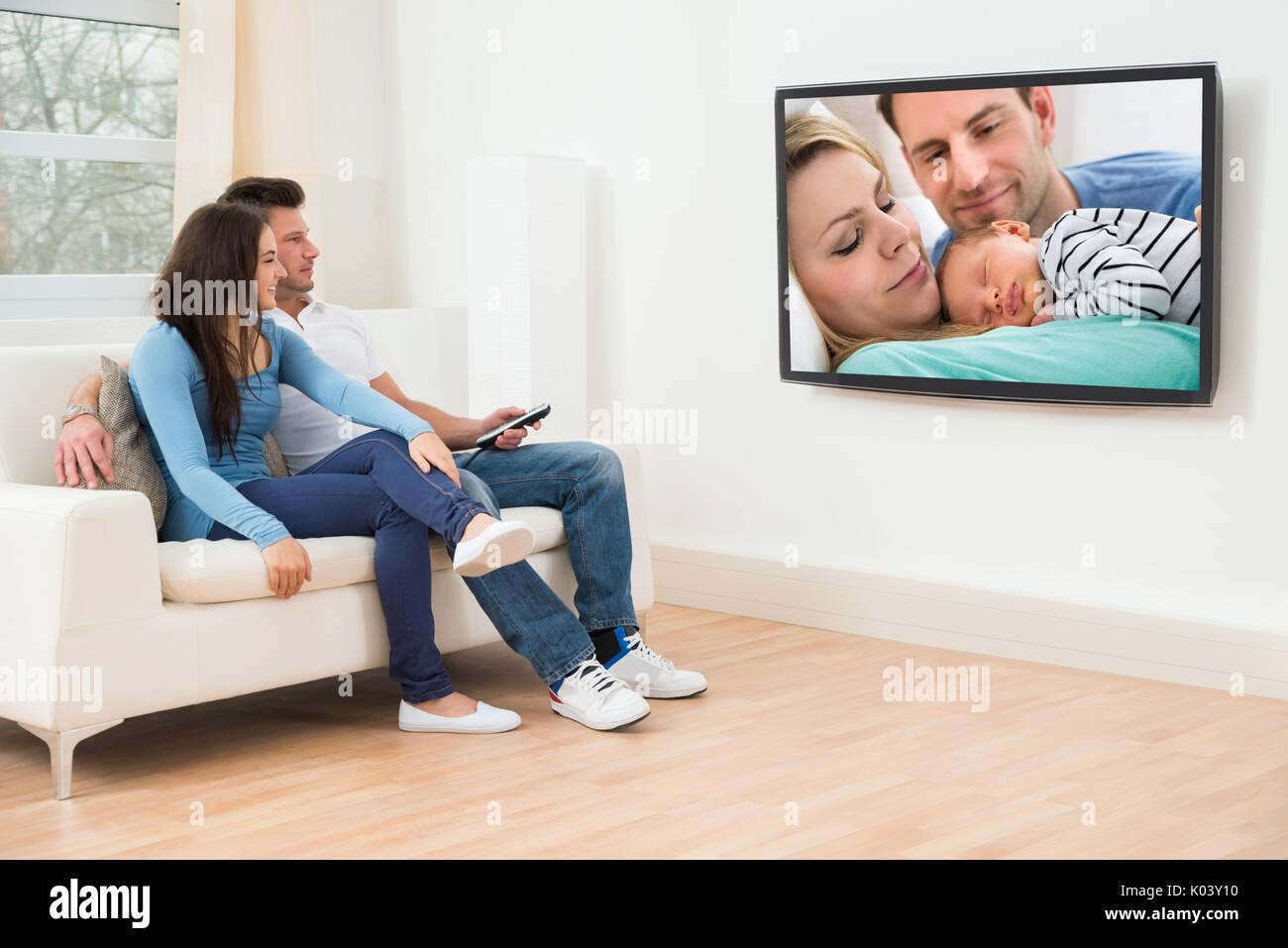 Junges Paar im Wohnzimmer auf der Couch vor dem Fernseher sitzen ...