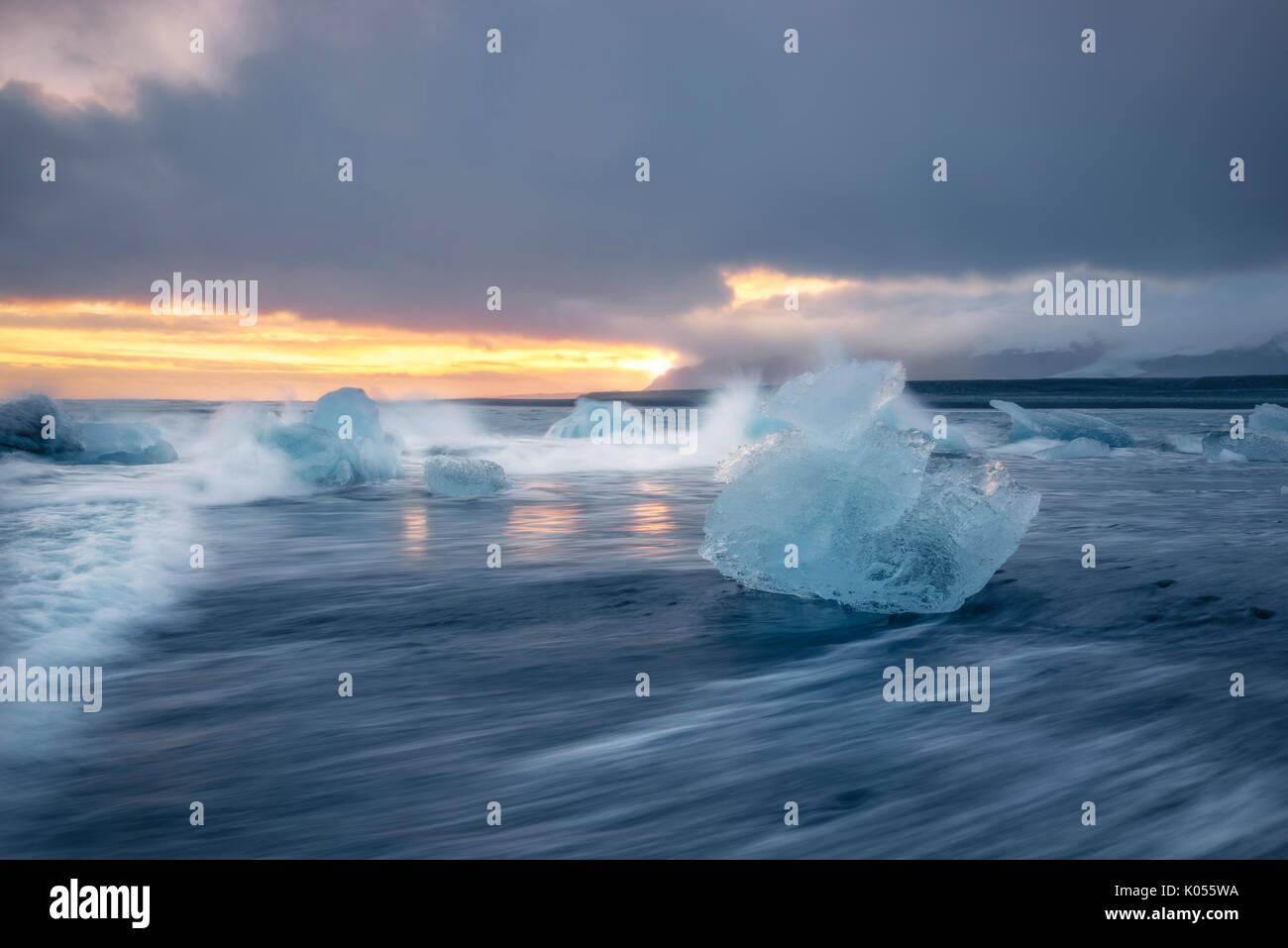 Eisblock am schwarzen Strand von Gletscherlagune Jökulsárlón bei einem Sonnenuntergang, Ost-Island, Europa Stockfoto
