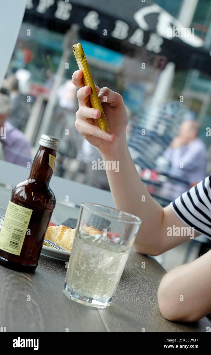 Junge Teenager mit männlichen Handy im Cafe Stockbild