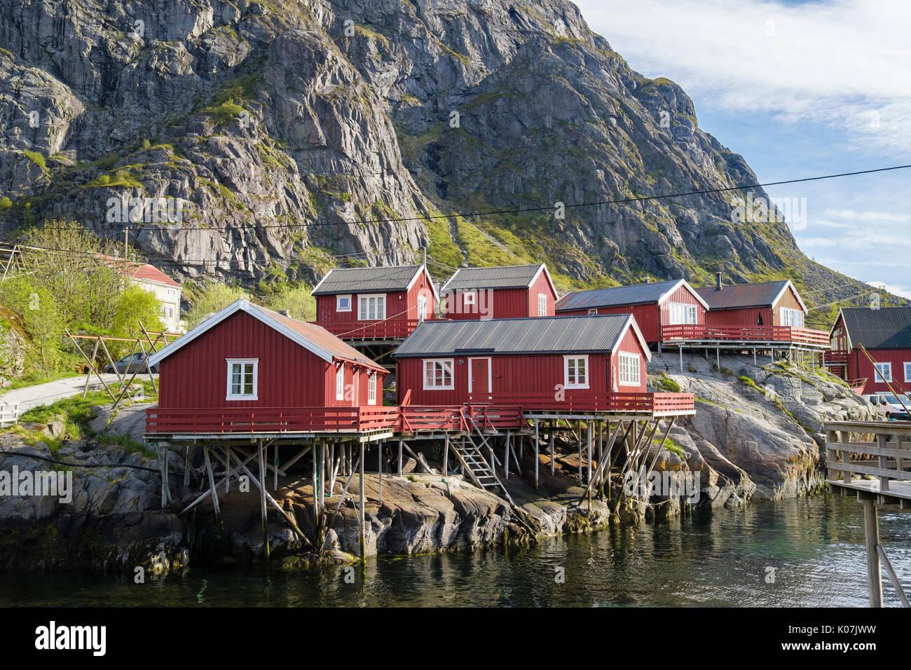 Der rote hölzerne Rorbuer Fischerhütten und Gebäude auf Stelzen durch Wasser im Fischerdorf Å, Moskenes, Insel Moskenesøya, Lofoten, Norwegen Stockbild
