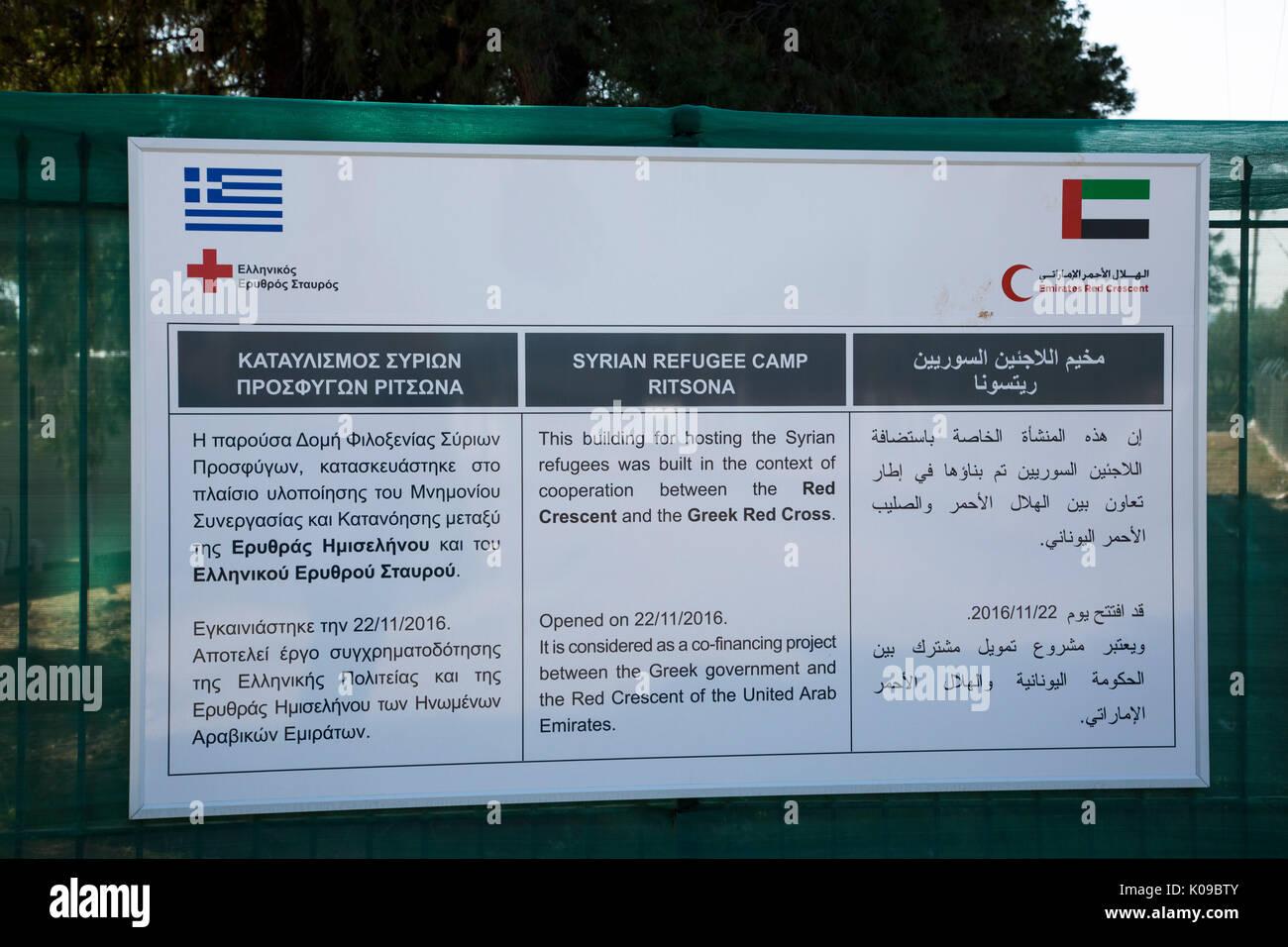 Ein Schild am Eingang Ritsona Flüchtlingslager in Griechisch, Englisch und Arabisch erzählt von Zusammenarbeit der Griechischen Roten Kreuz und Roten Halbmond Emirates. Stockbild
