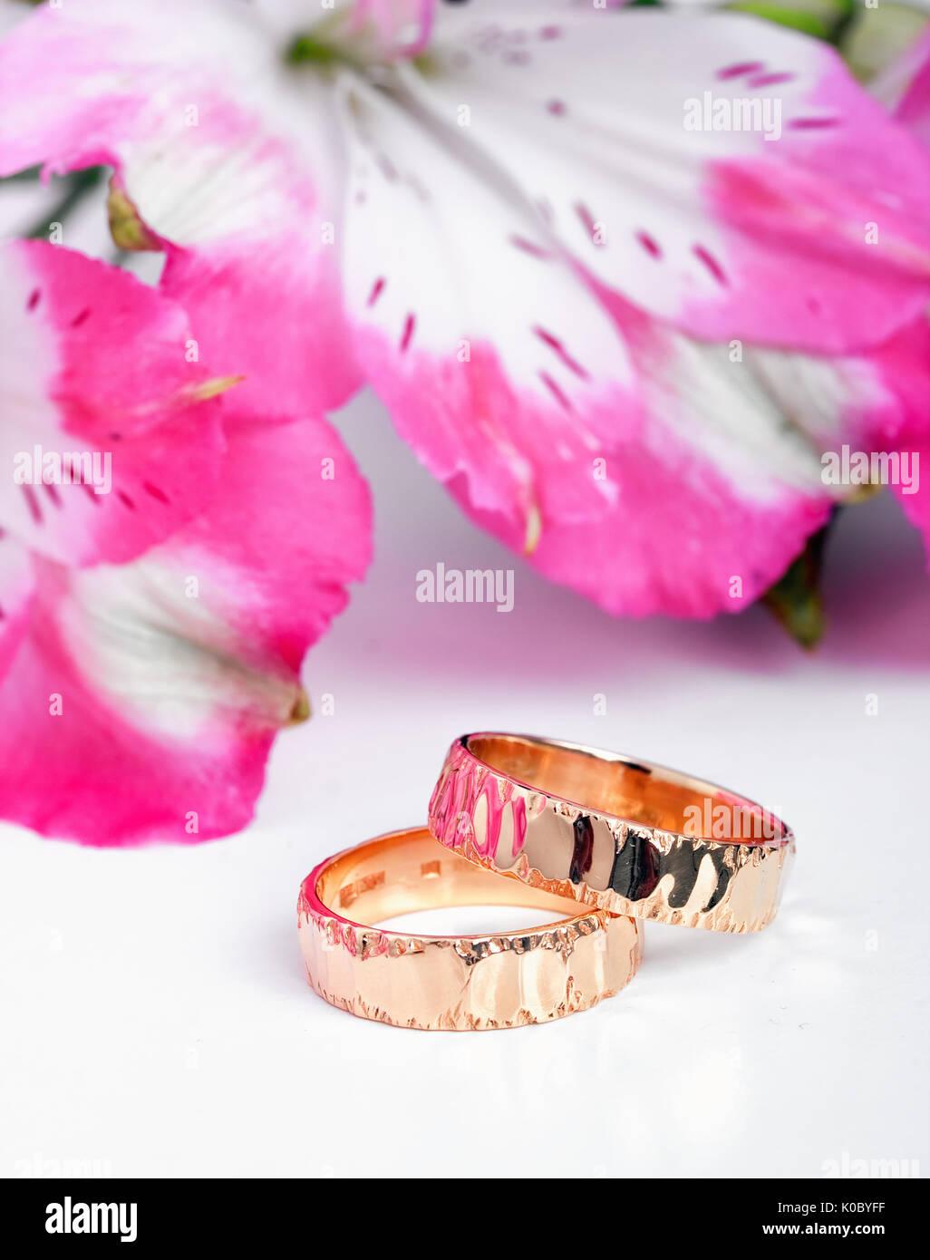 Ein Paar Goldene Hochzeit Ringe Mit Rosa Blumen Im Hintergrund