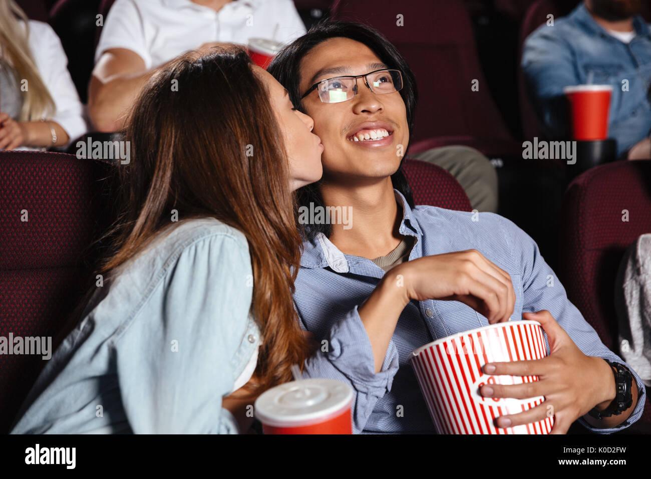 Image der jungen Liebenden paar sitzen im Kino film ansehen und küssen Stockbild