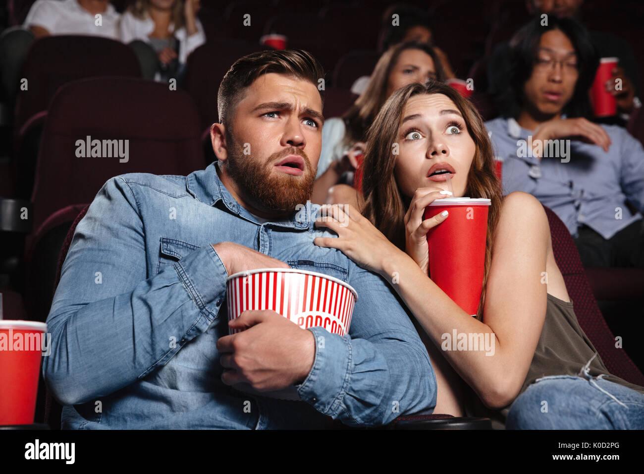 Junge Angst paar Beobachten ein Horror Film, während im Kino mit Popcorn Stockfoto