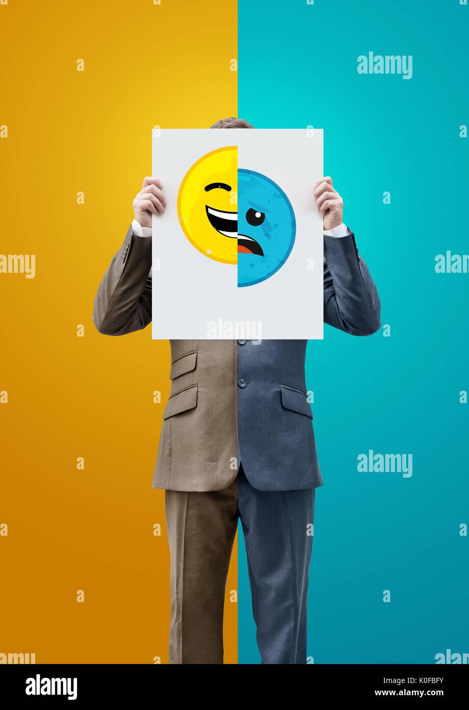 Geschäftsmann Holding glücklich und traurig Emoticon Gesichter. Konzept Stockbild