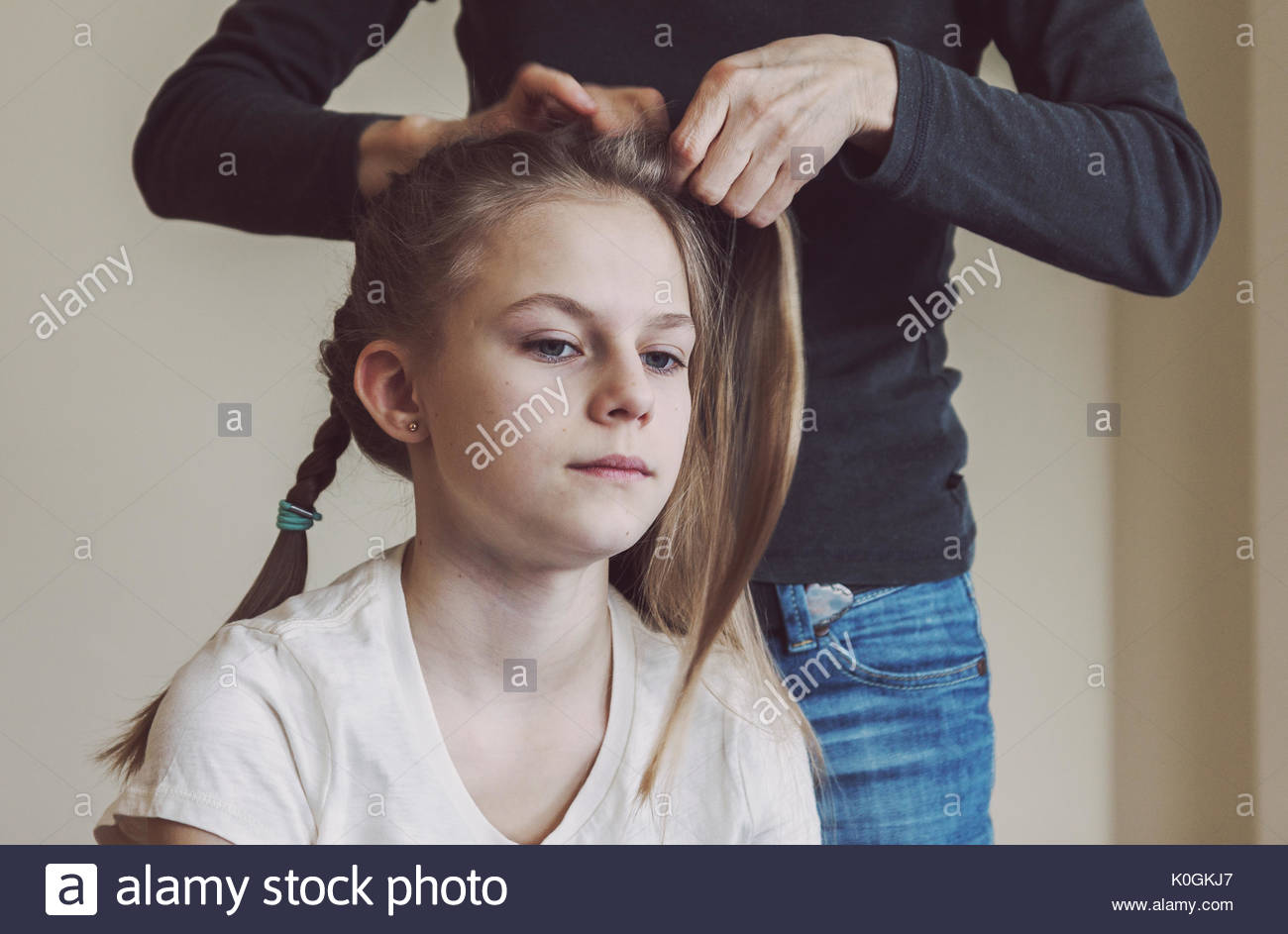 Mutter flechten junge Mädchen Haare. Real Life Porträt Bild der kaukasischen jugendlich Mädchen mit gezielten warm mate Filter Stockbild