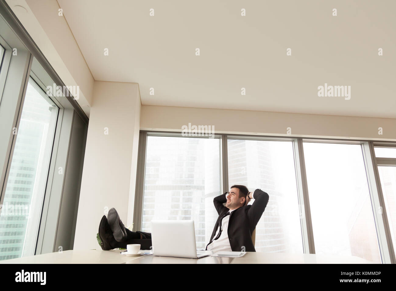 Geschäftsmann entspannen im Büro mit Füßen auf Schreibtisch, Copyspace Stockbild