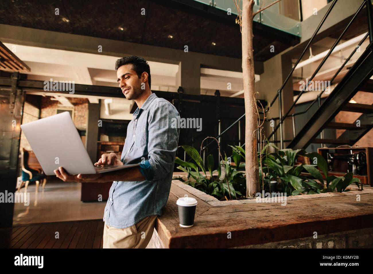 Schuß von jungen kreativen Menschen in Unternehmen lounge Arbeiten am Laptop. Unternehmer im modernen Büro mit Laptop. Stockbild