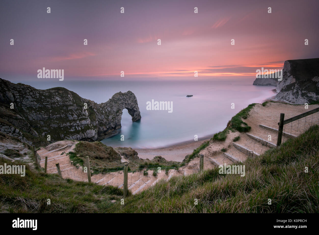Eine dramatische magenta Sonnenuntergang auf einer Sommer Abend an Durdle Door auf der Jurassic Coast in Dorset, ein Weltkulturerbe mit einer langen Belichtungszeit genommen Stockbild