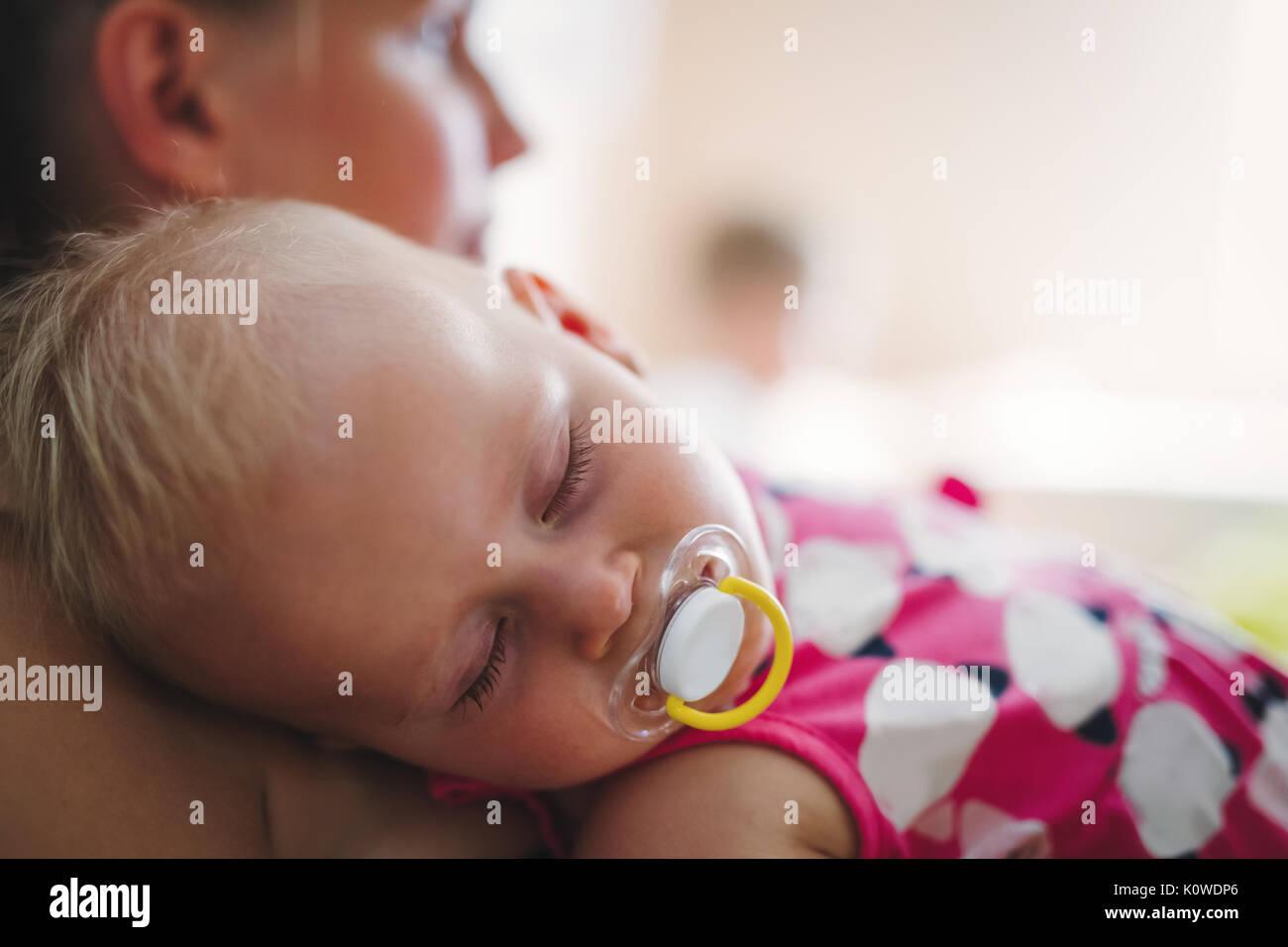 Junge Mutter hält ihr schlafendes Neugeborenes Stockbild