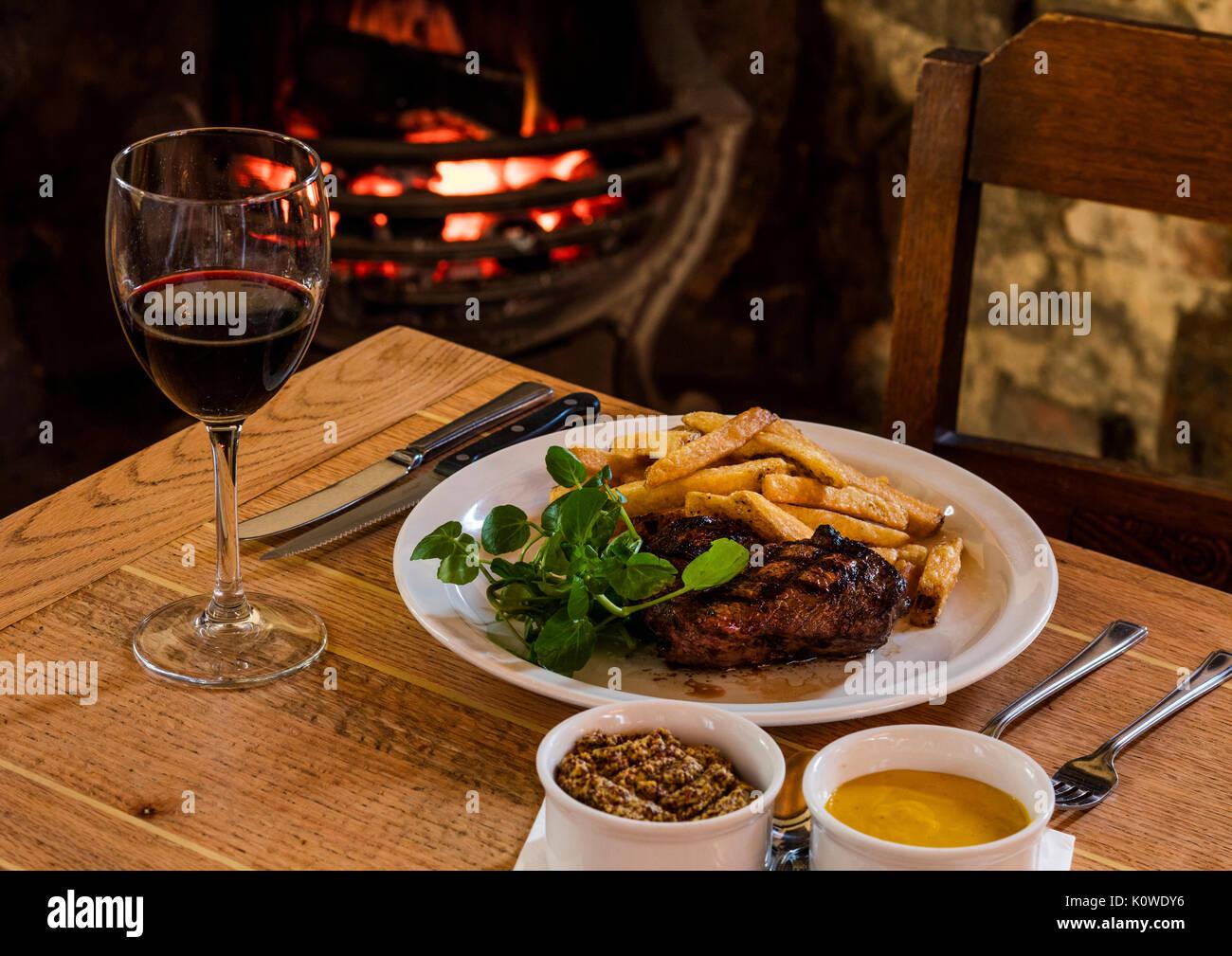 Steak und Chips am Kamin Stockbild