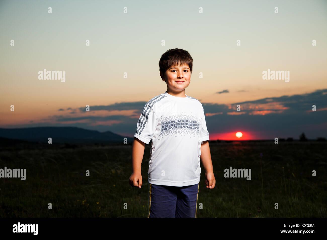Mutige Junge lächelnd gegen die Dämmerung mit Sun Stockbild