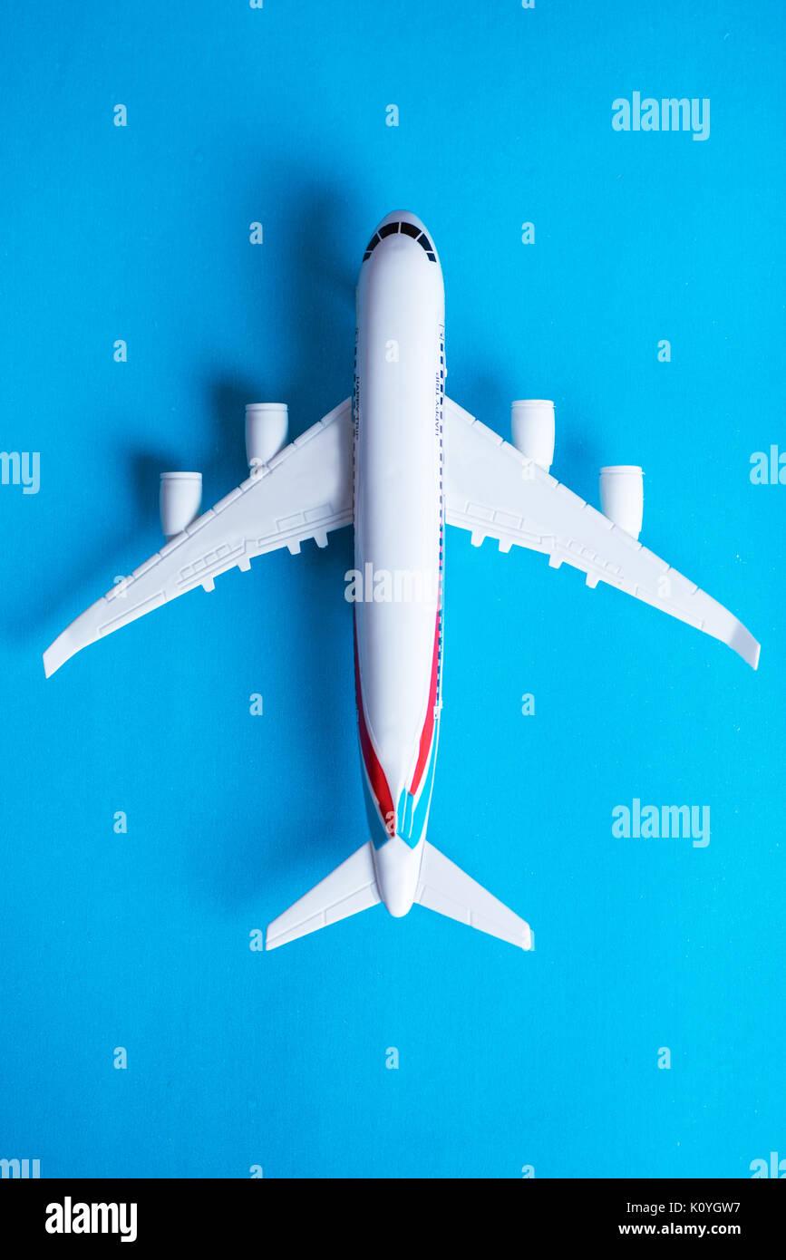 Miniatur Spielzeug Flugzeug auf blauem Hintergrund. Anreise mit dem Flugzeug Stockbild